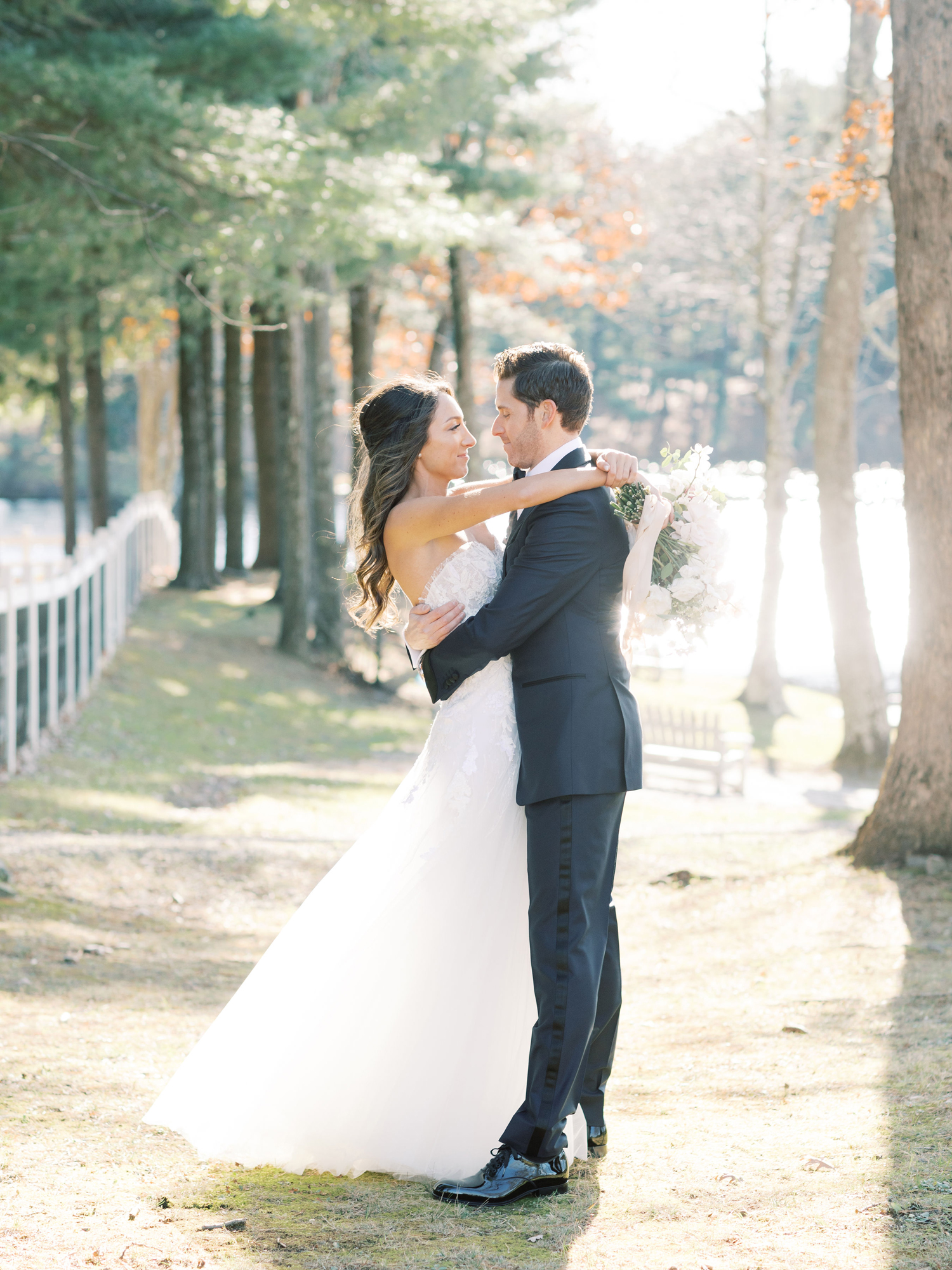 bride and groom hugging outside on grassy lawn near white fence