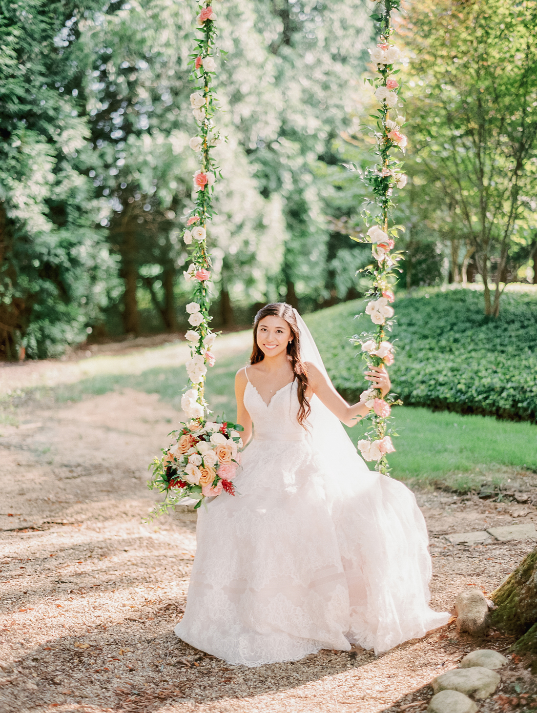 bride sitting on wooden swing covered in flowers