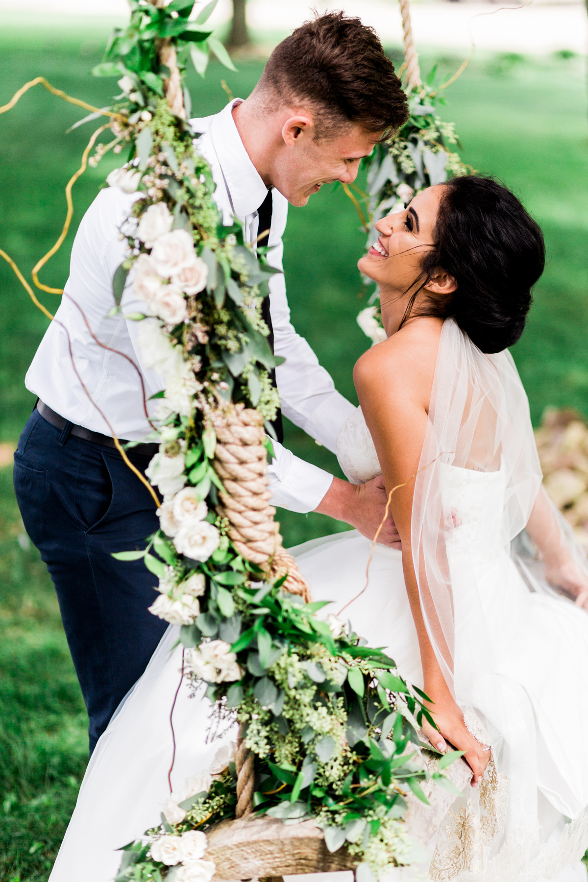 bride sitting on wooden swing with twine rope and flowers