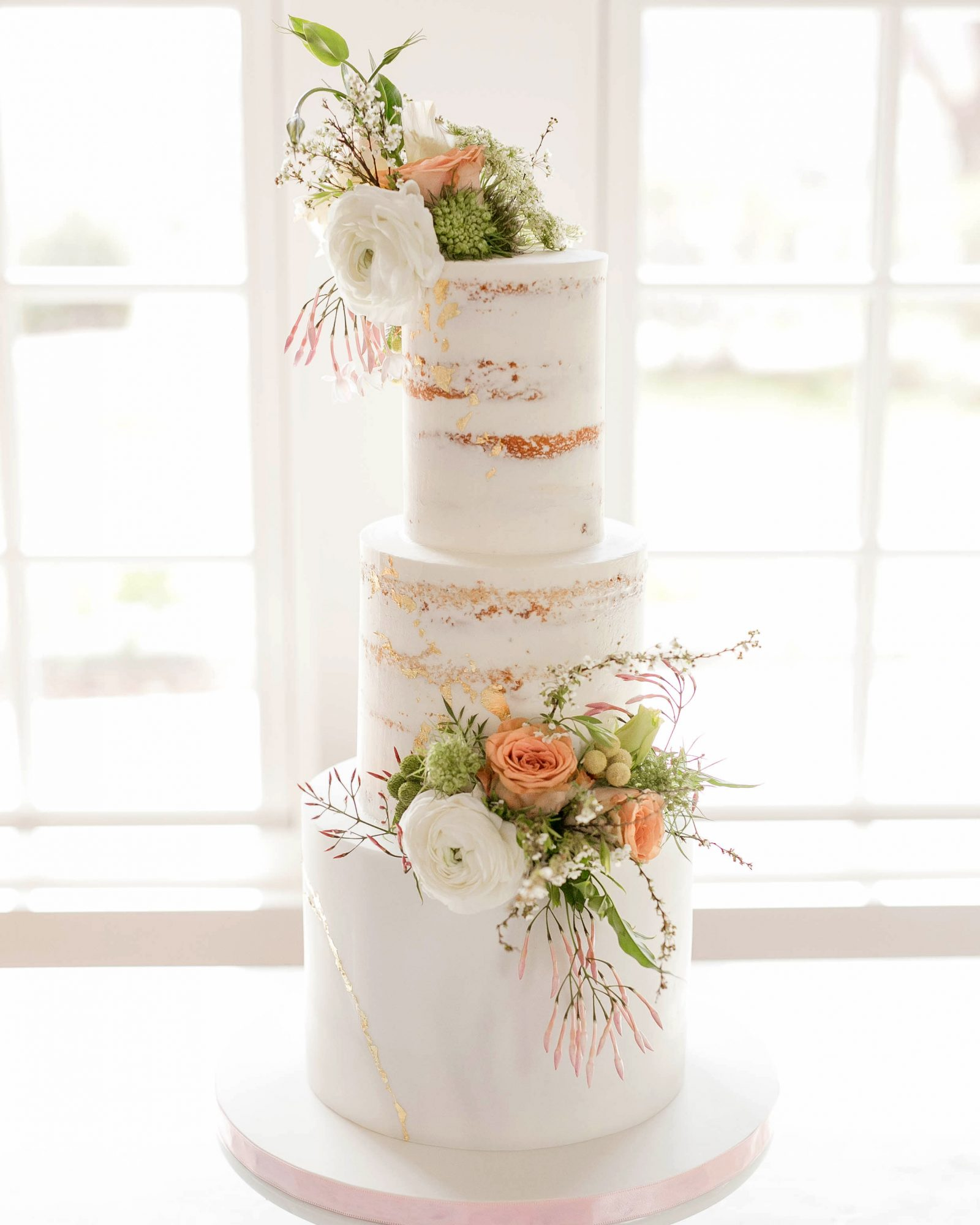 three tiered white frosted cake with floral decor
