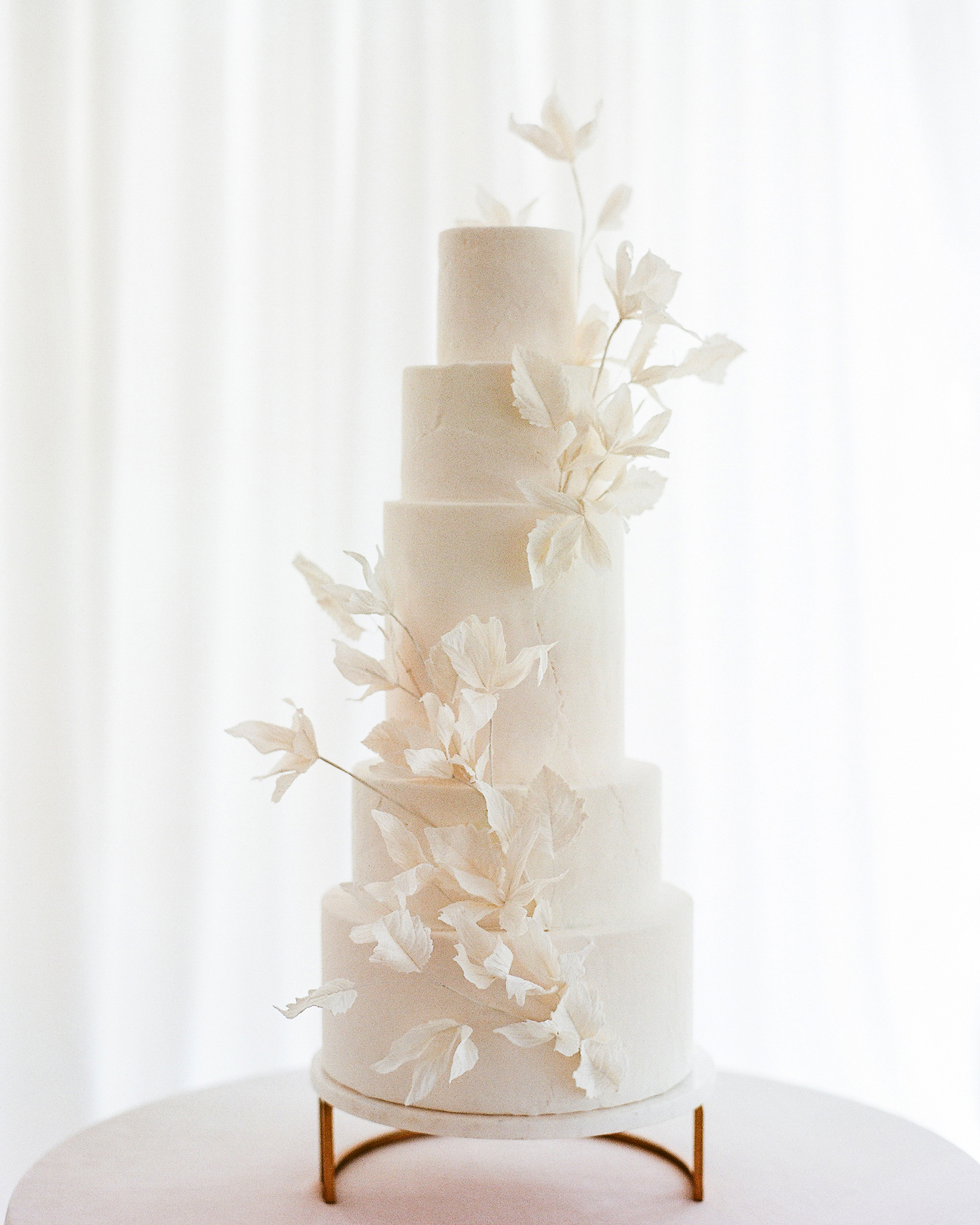 five tiered white frosted sugar flowers decor wedding cake