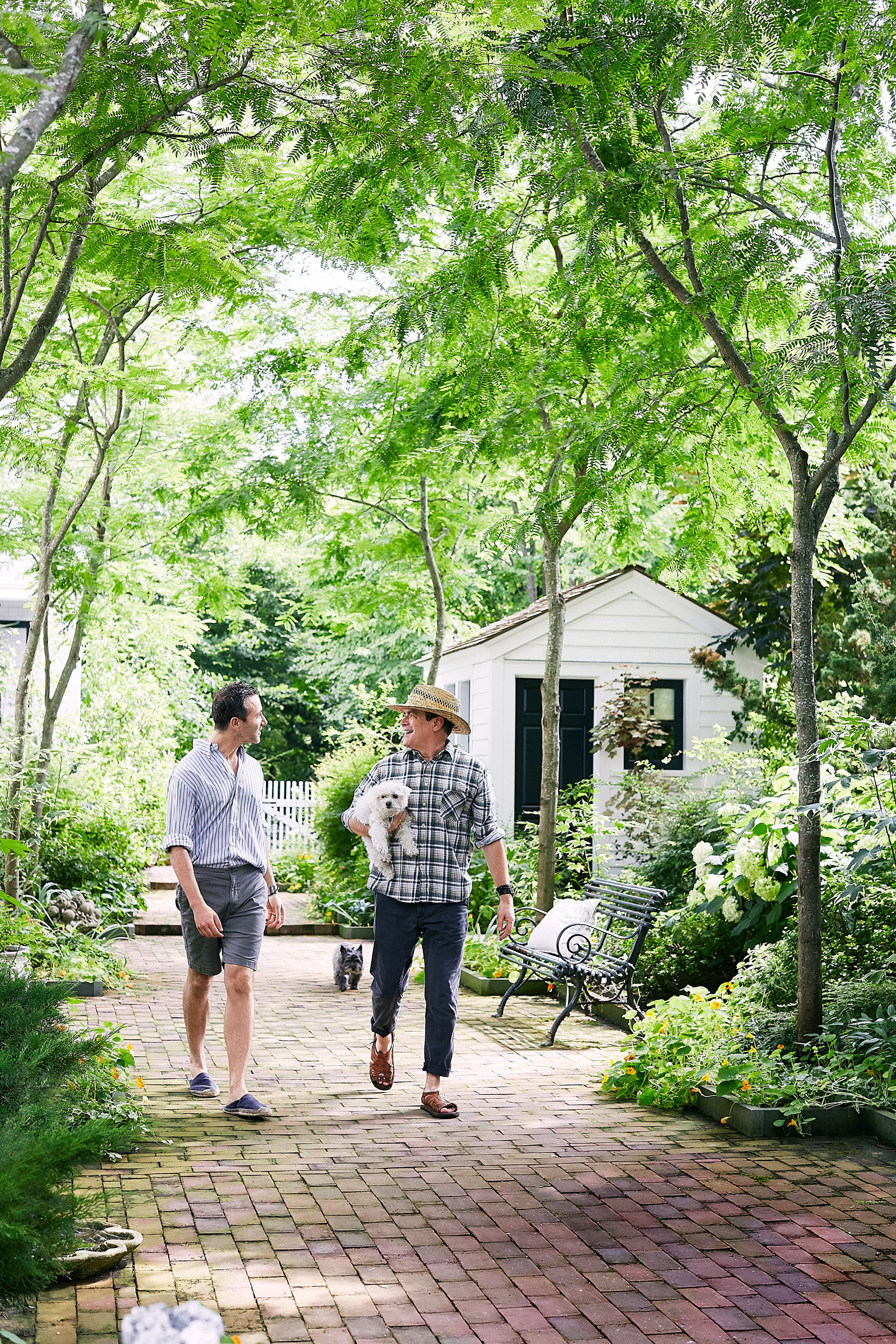 couple with dogs strolling through garden of weekend home