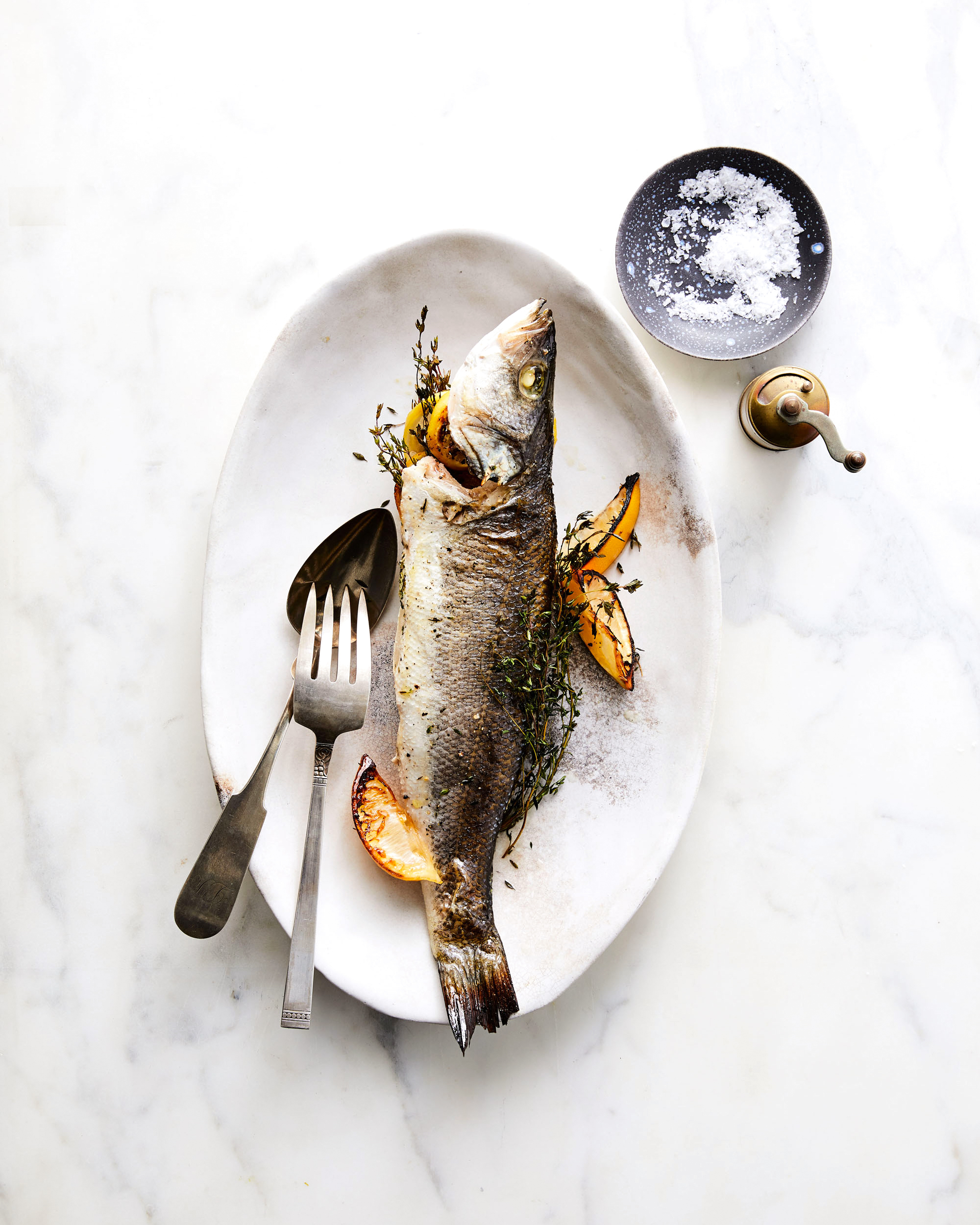 Whole-Roasted Branzino with Lemon and Thyme on plate with lemon wedges and silverware