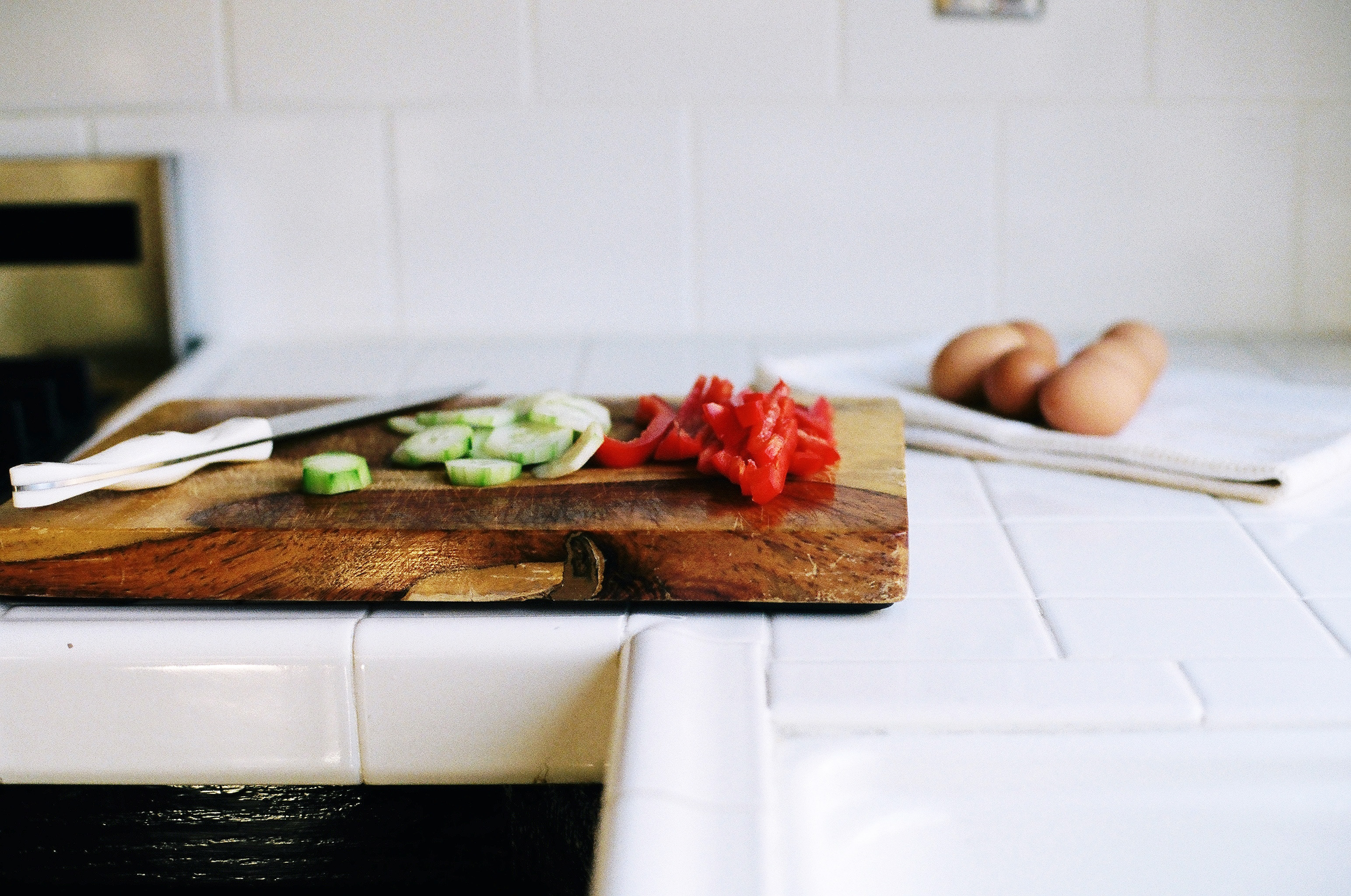 white ceramic countertop with cutting board and vegetables