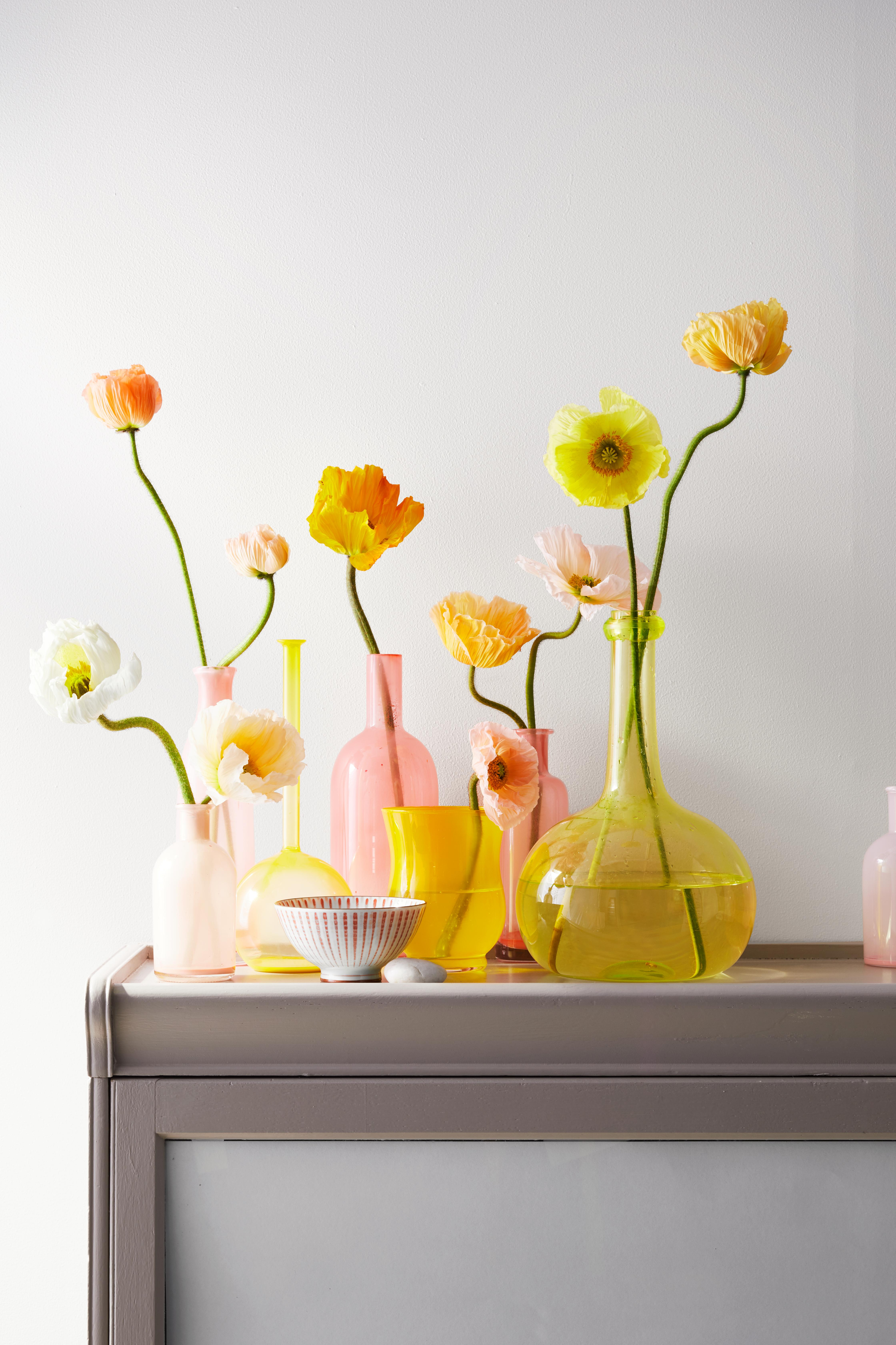 painted glass vases with flowers on gray stand