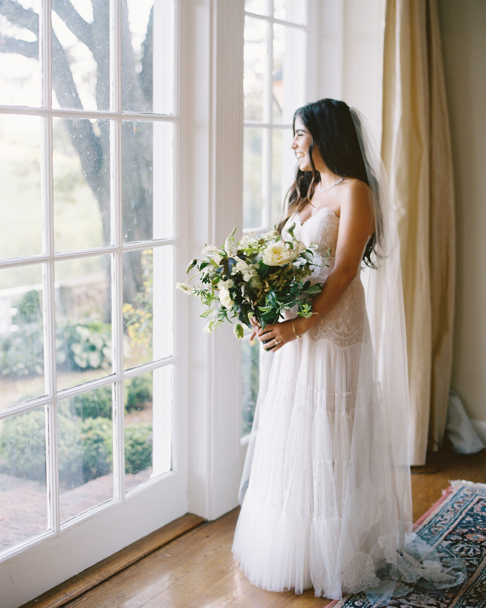 bride looking out window in gown holding white floral bouquet