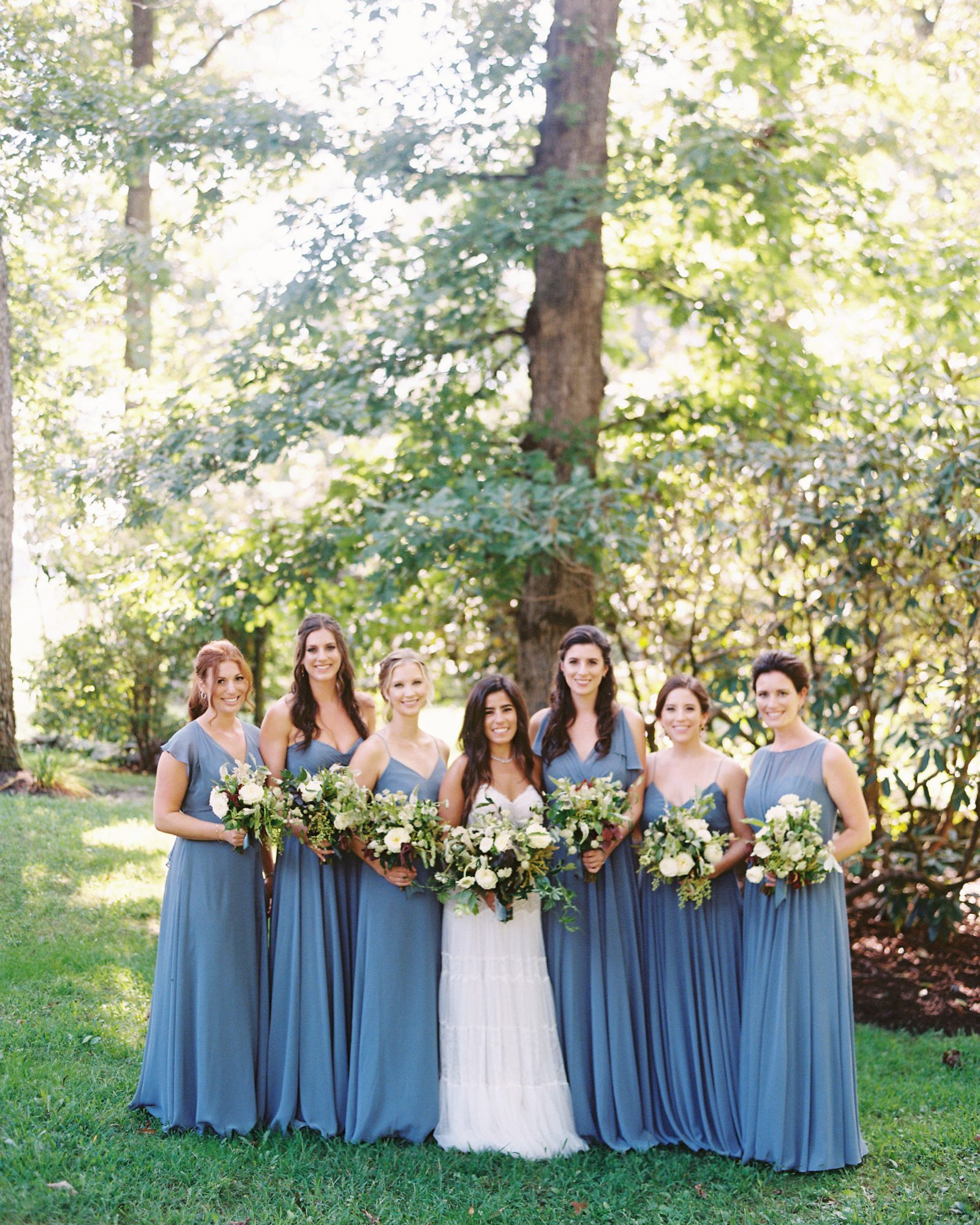 bride and bridesmaids pose outdoors in blue dresses