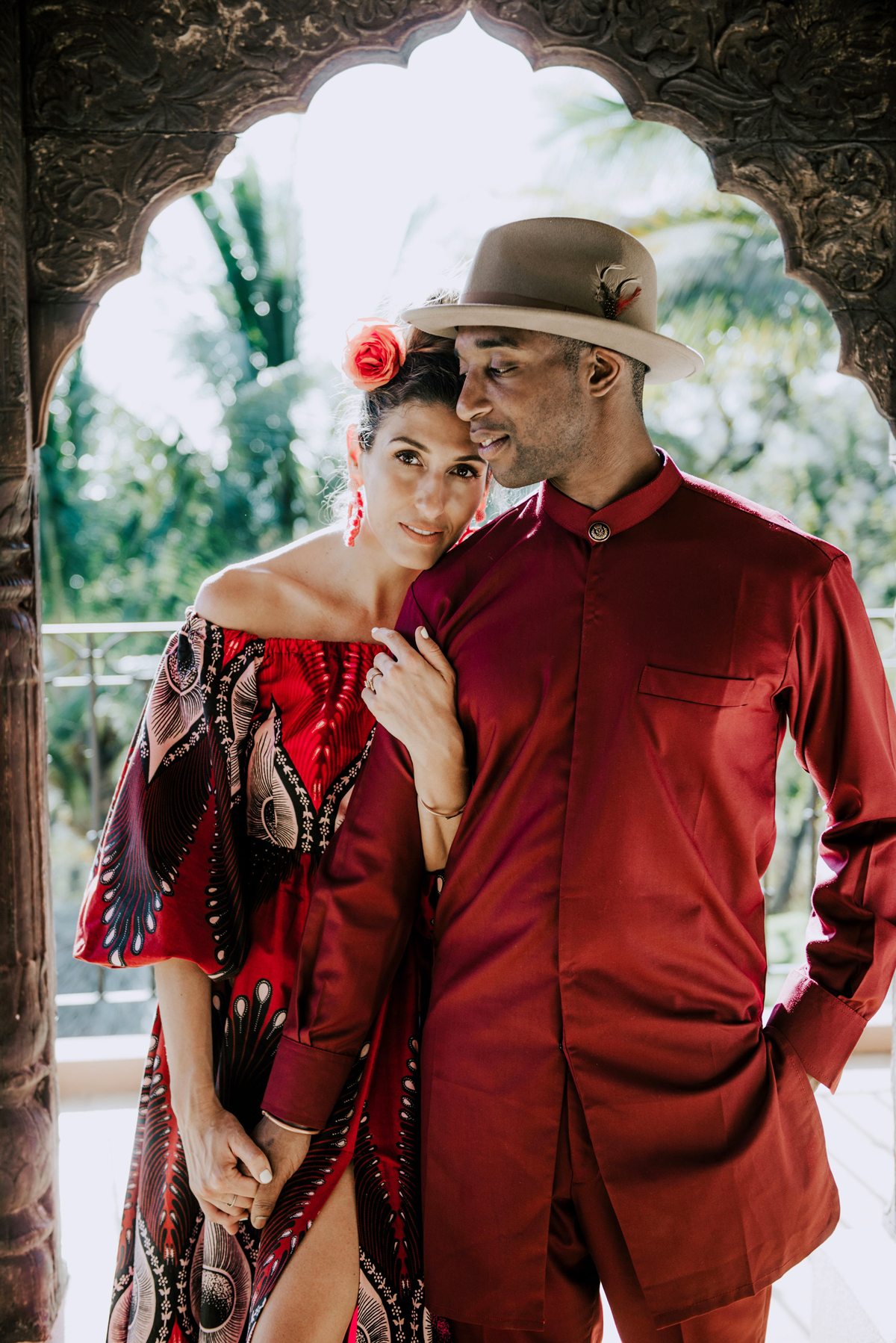 bride and groom pose for portrait photo wearing matching red outfits