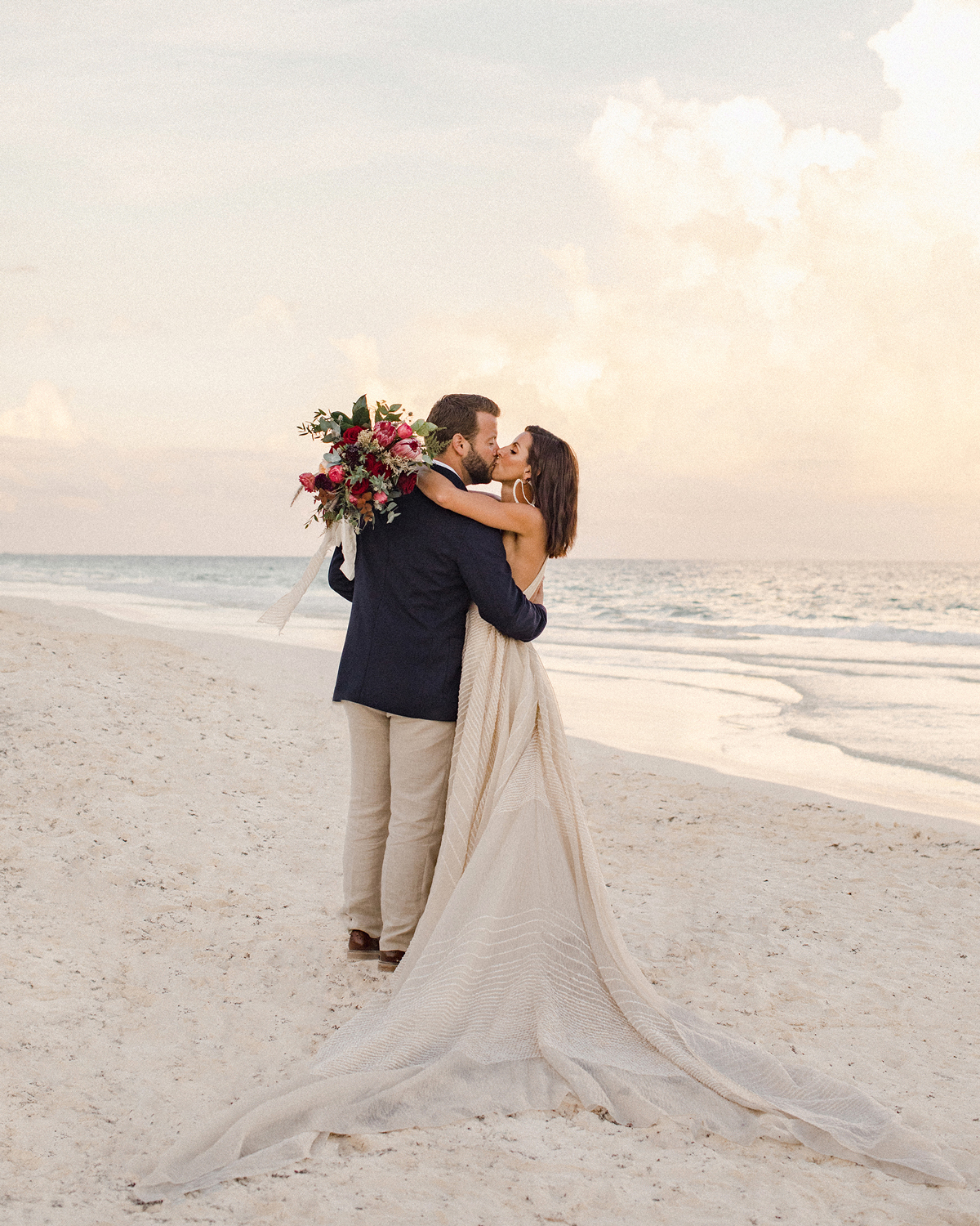 sunset wedding photos bride and groom kissing on beach