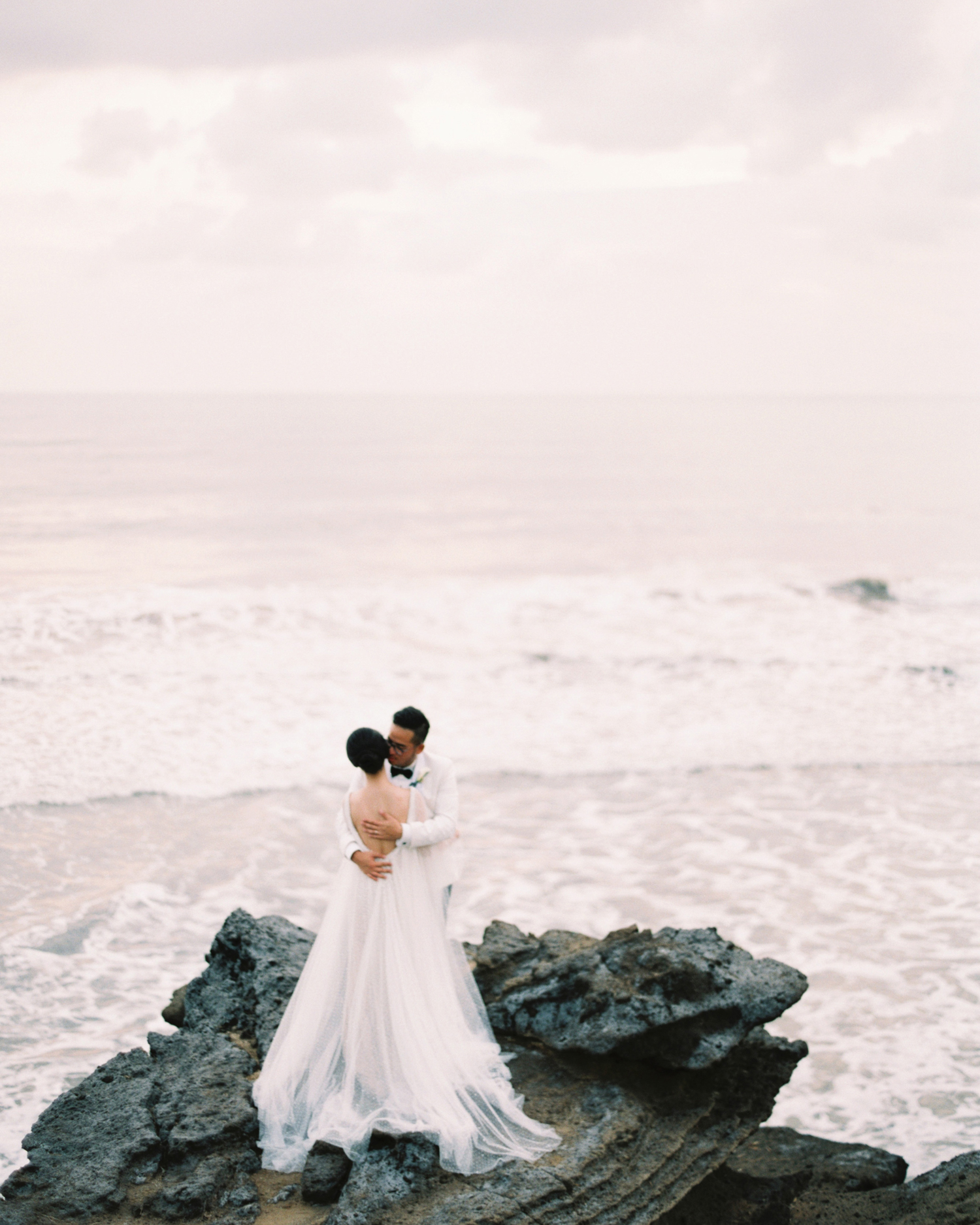 sunset wedding photos bride and groom embracing on oceanic cliff