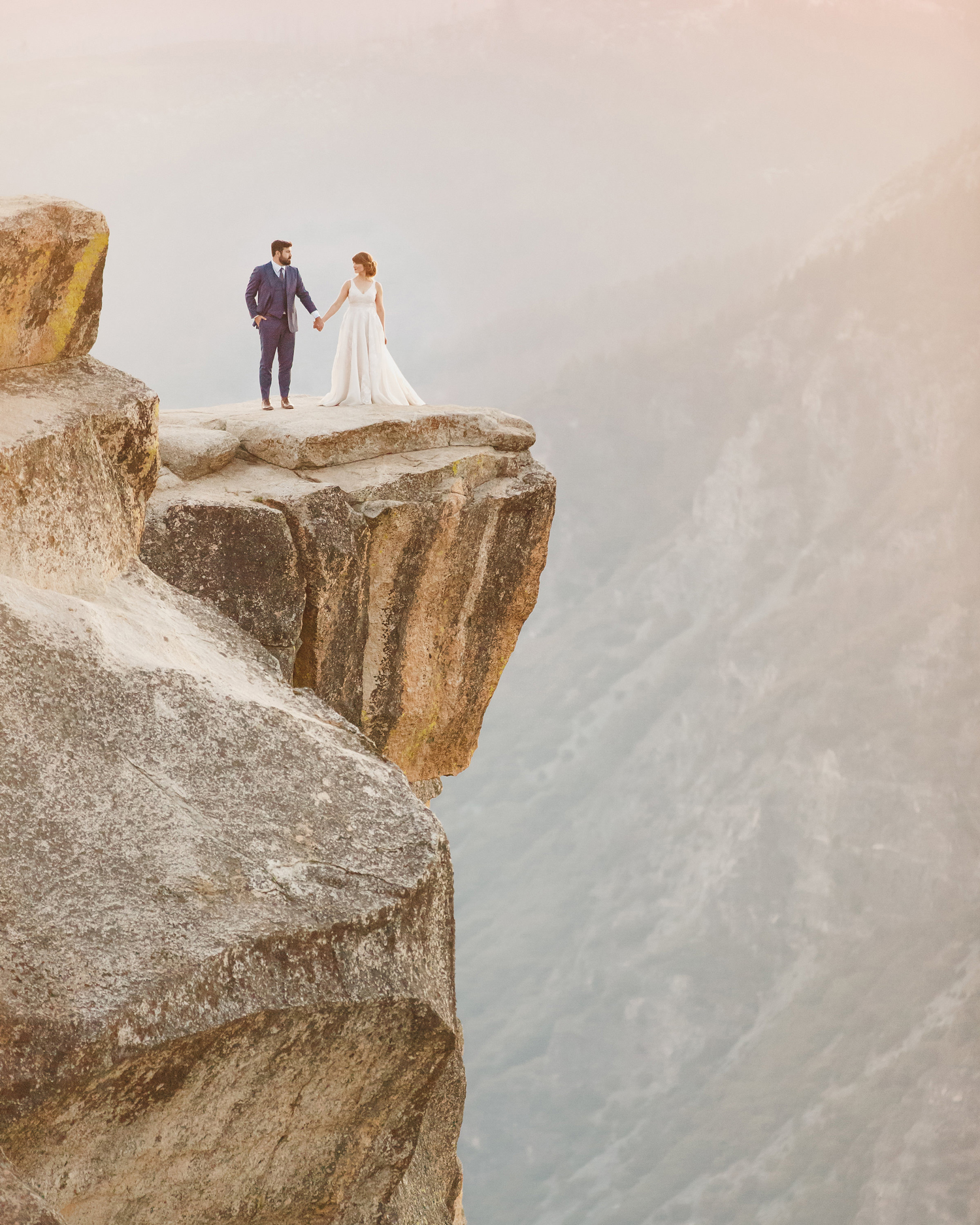 sunset wedding photos bride and groom holding hands on cliff at yosemite national park