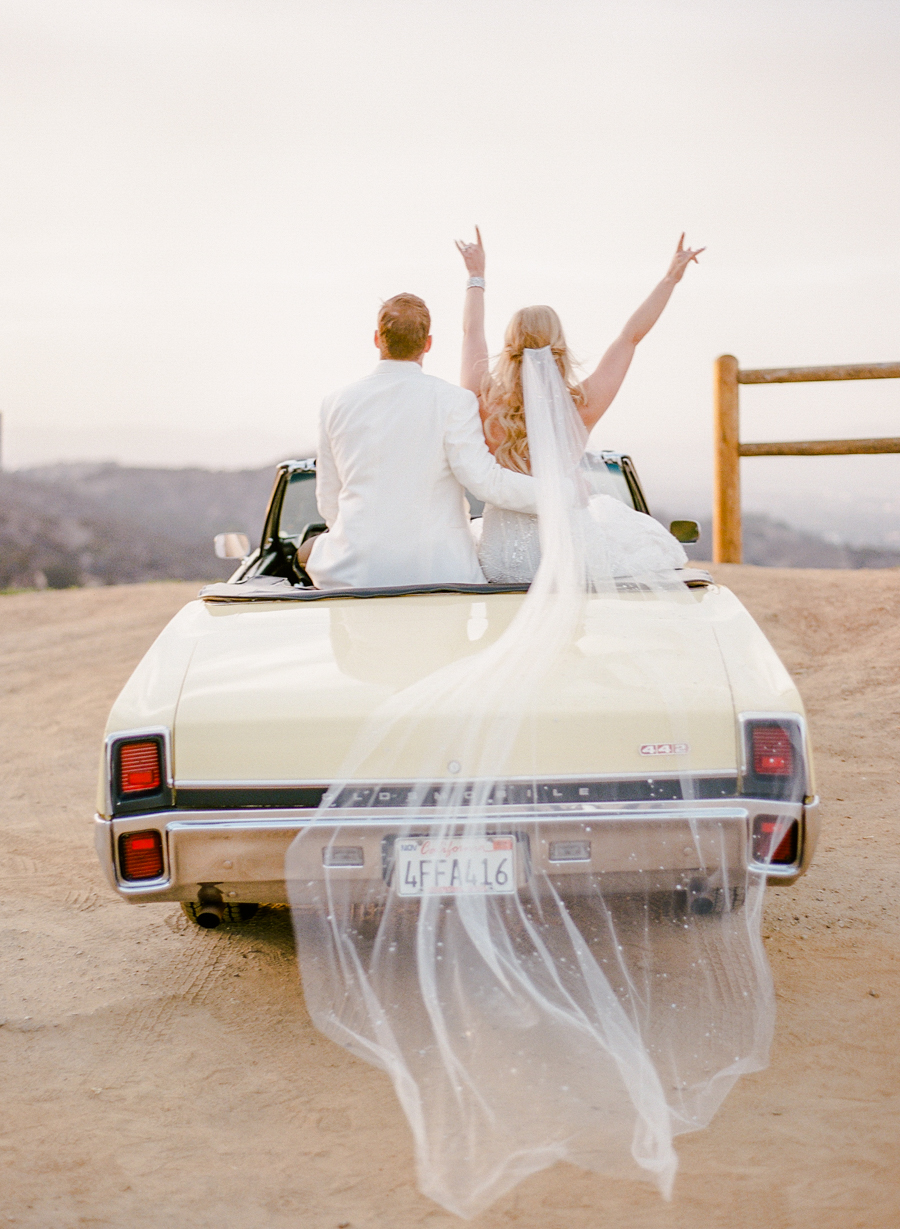 sunset wedding photos bride and groom in getaway car overlooking los angeles