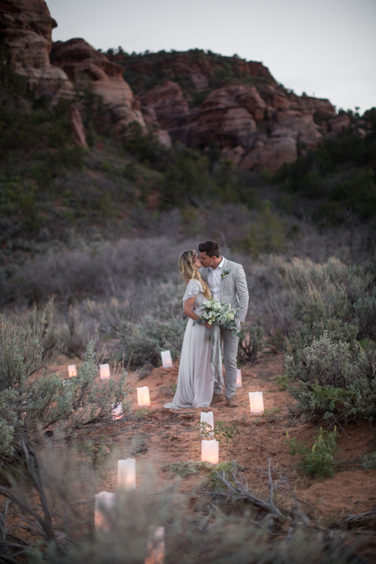sunset wedding photos bride and groom kissing amongst candles in desert