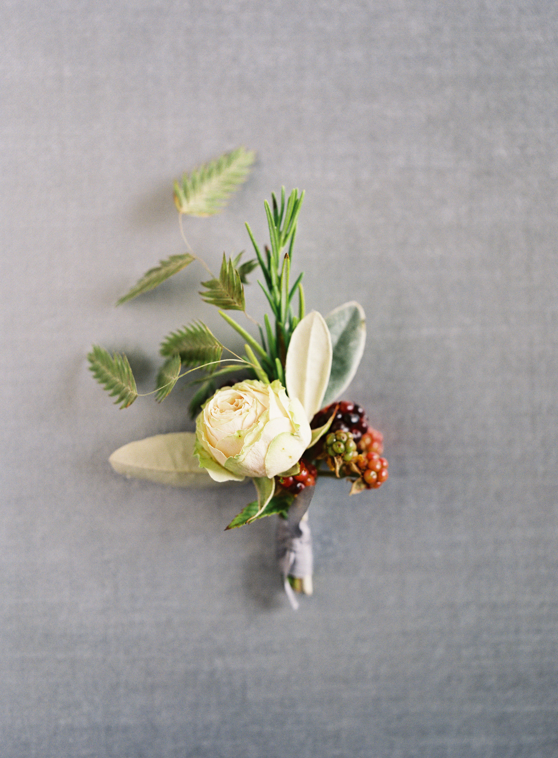 white bloom, berries, and green foliage boutonnieres