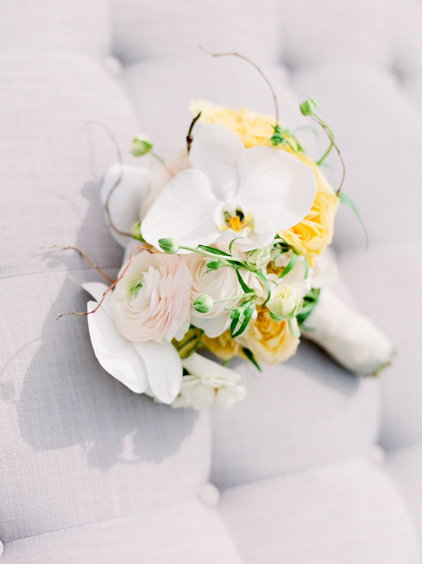white, yellow, and blush orchids, peonies, hydrangeas, ranunculus and spray roses bouquet