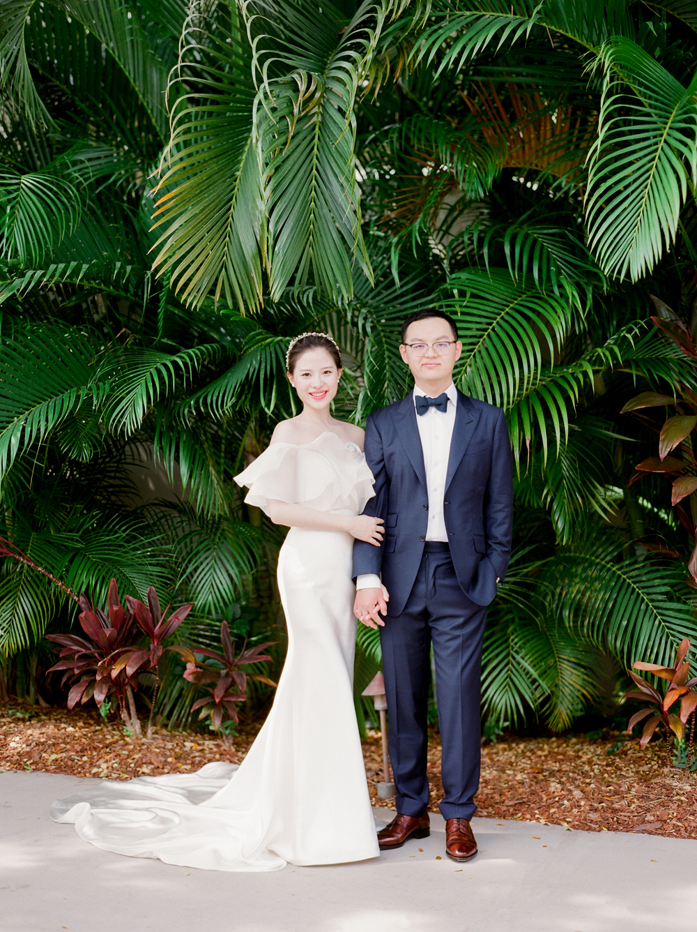 bride and groom standing in front of large leaf tropical plants outside