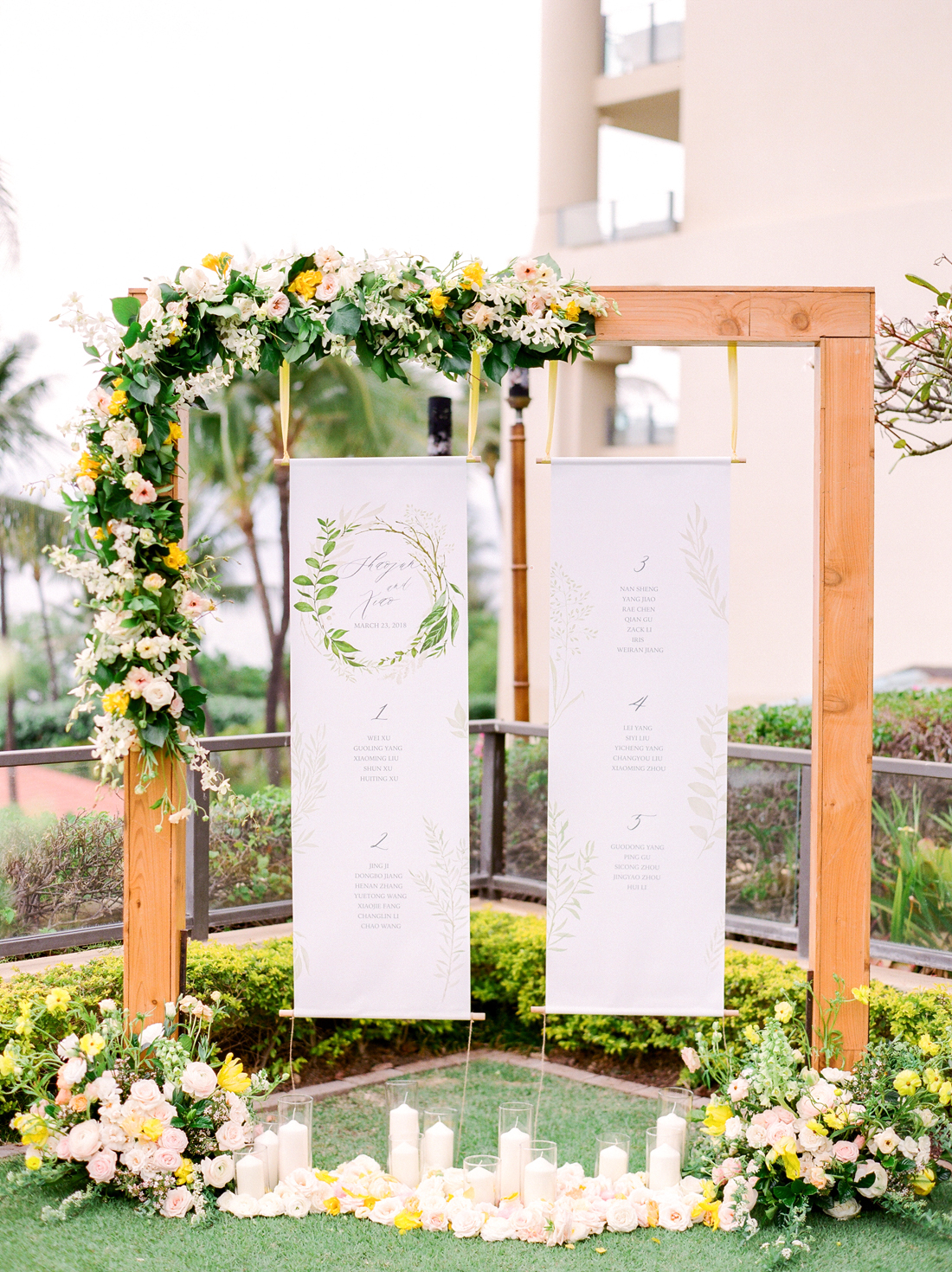 white hanging calligraphy seating chart on cedar arch