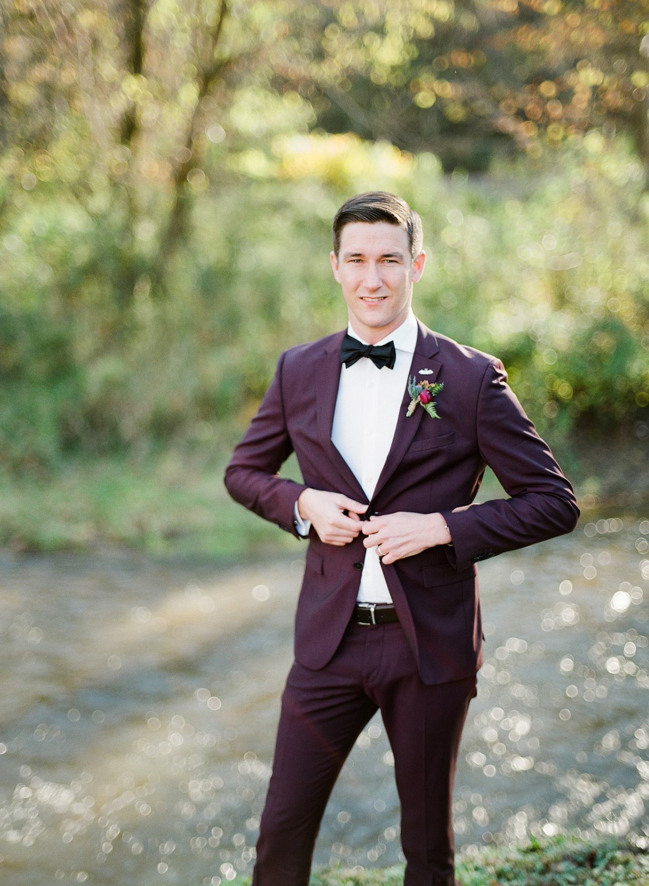 groom wearing burgundy suit, fitted white dress shirt, and black bow tie