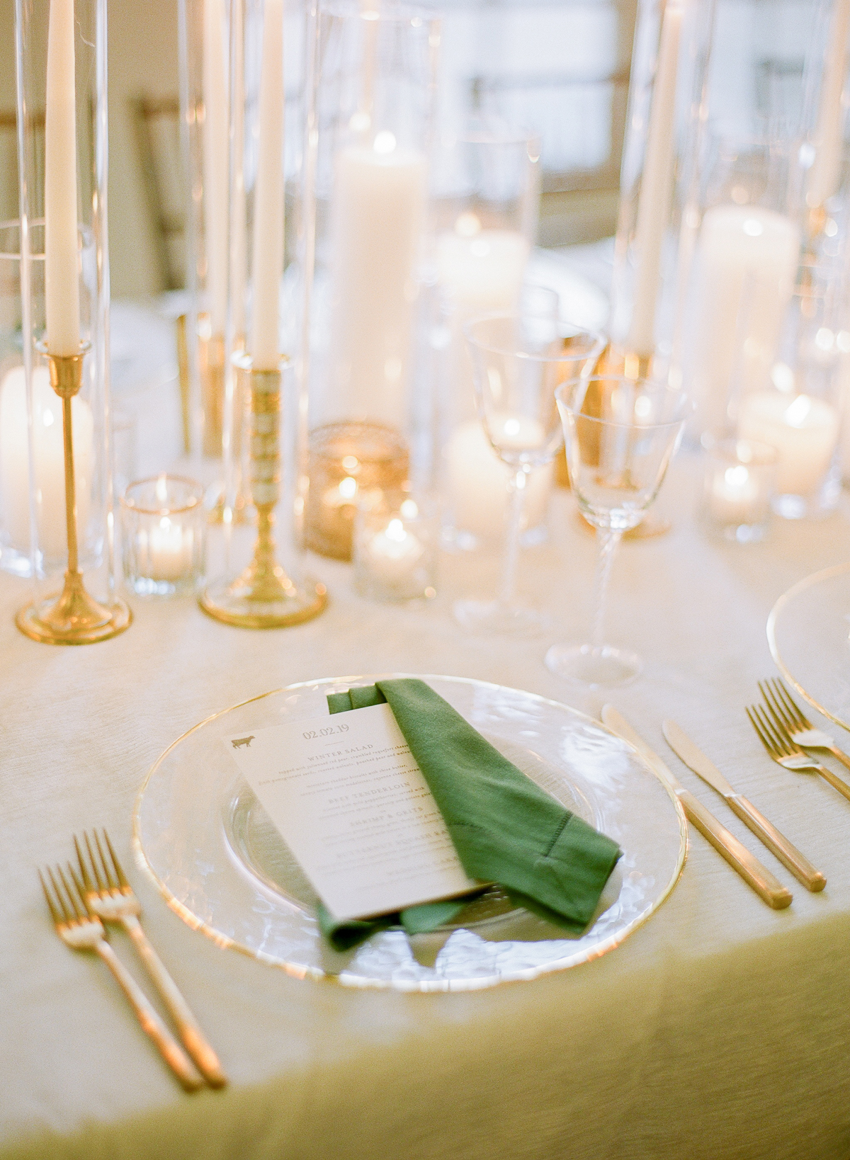 ivory cardstock menus on green linen napkins and gold tableware