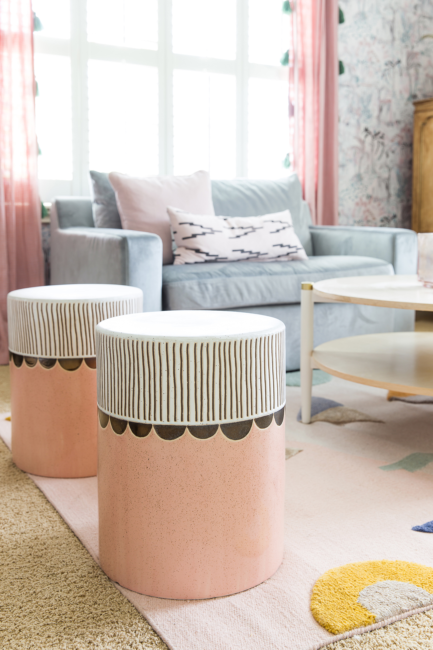 blue-gray couch and pink stools in bedroom