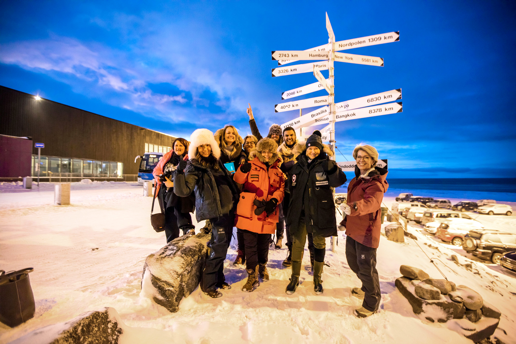 martha with group of explorers under sign pointing to major cities