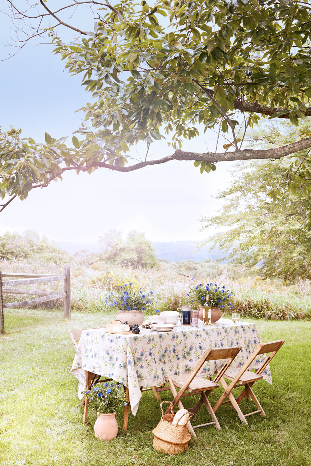 outdoor picnic table under tree by wooden fence