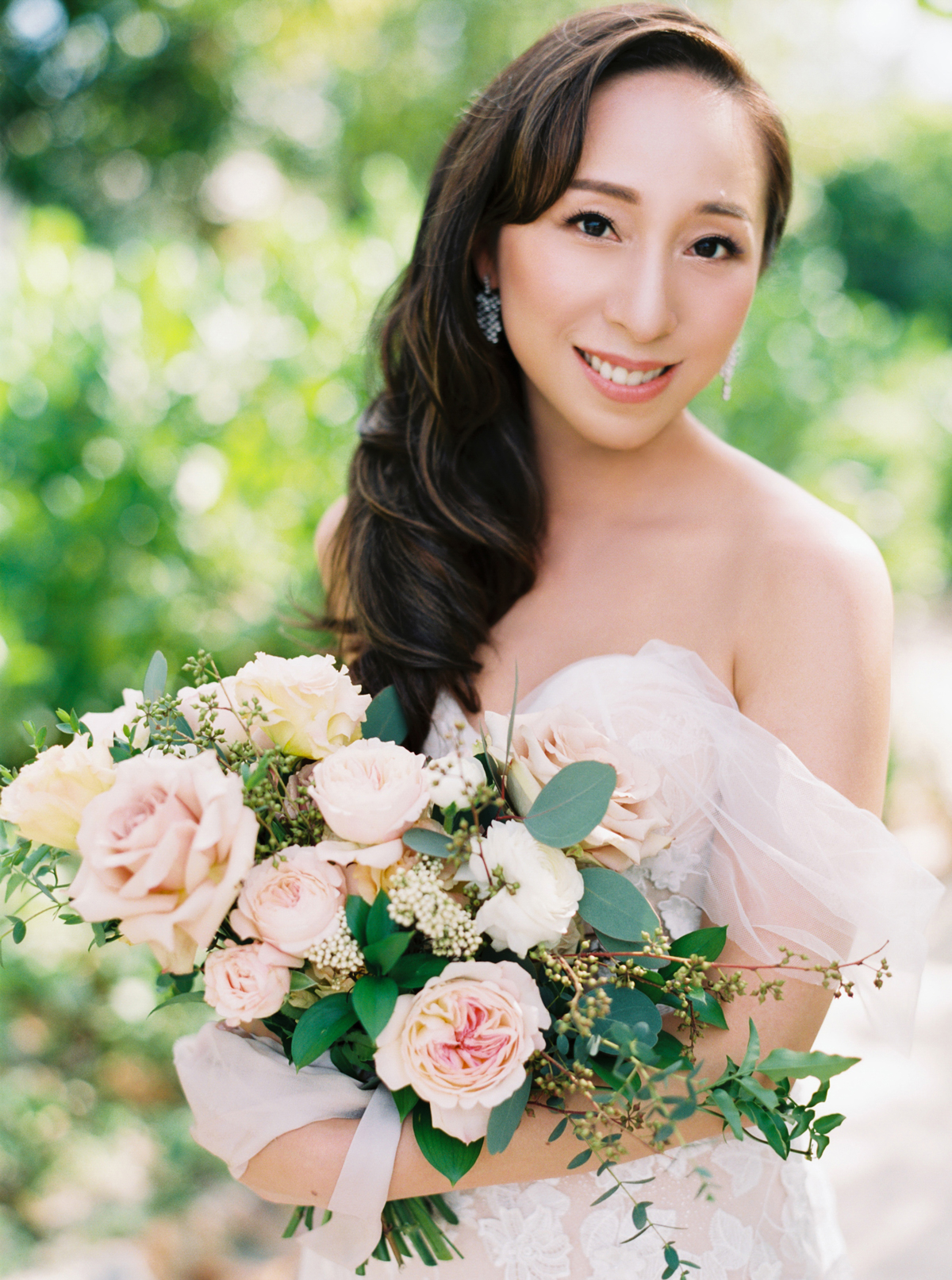 bride holding blush and peach-colored roses bouquet