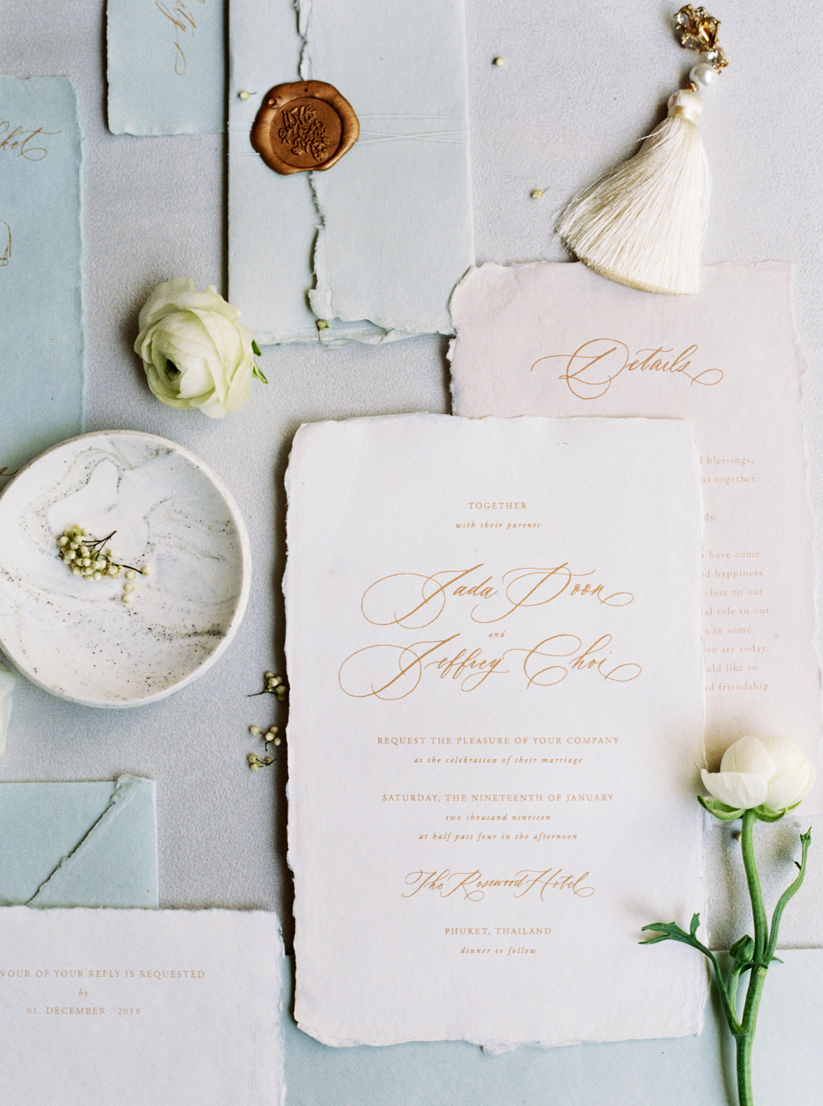 gold script on ivory and blush paper with torn edges invites