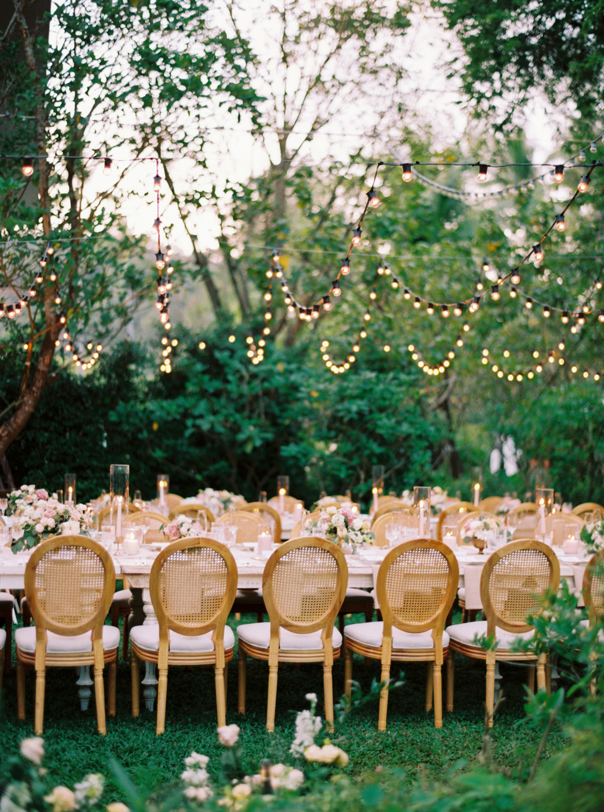 long tables with wooden chairs and string lights reception