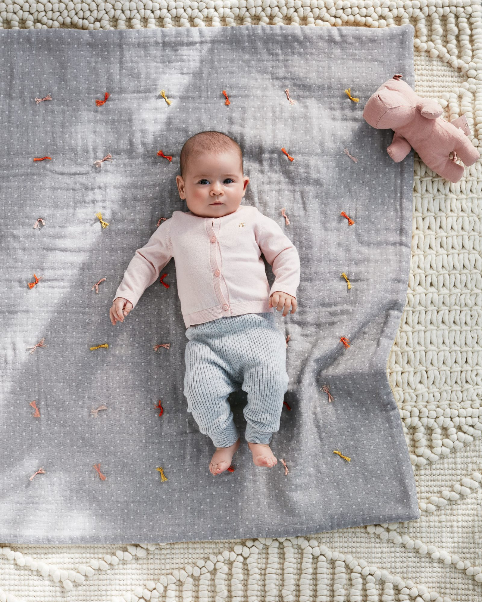 baby on a quilt with knots