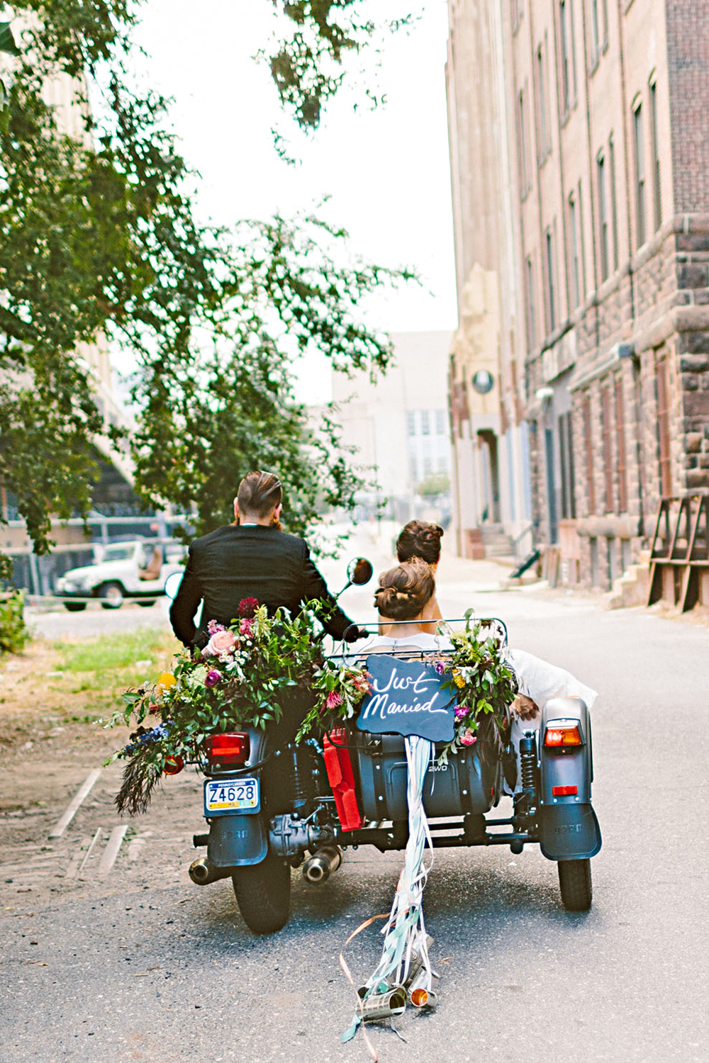 The newlyweds' Ural motorcycle—which inspired their logo—was decked out for the big day. They snuggled in the sidecar while a friend drove to the venue.