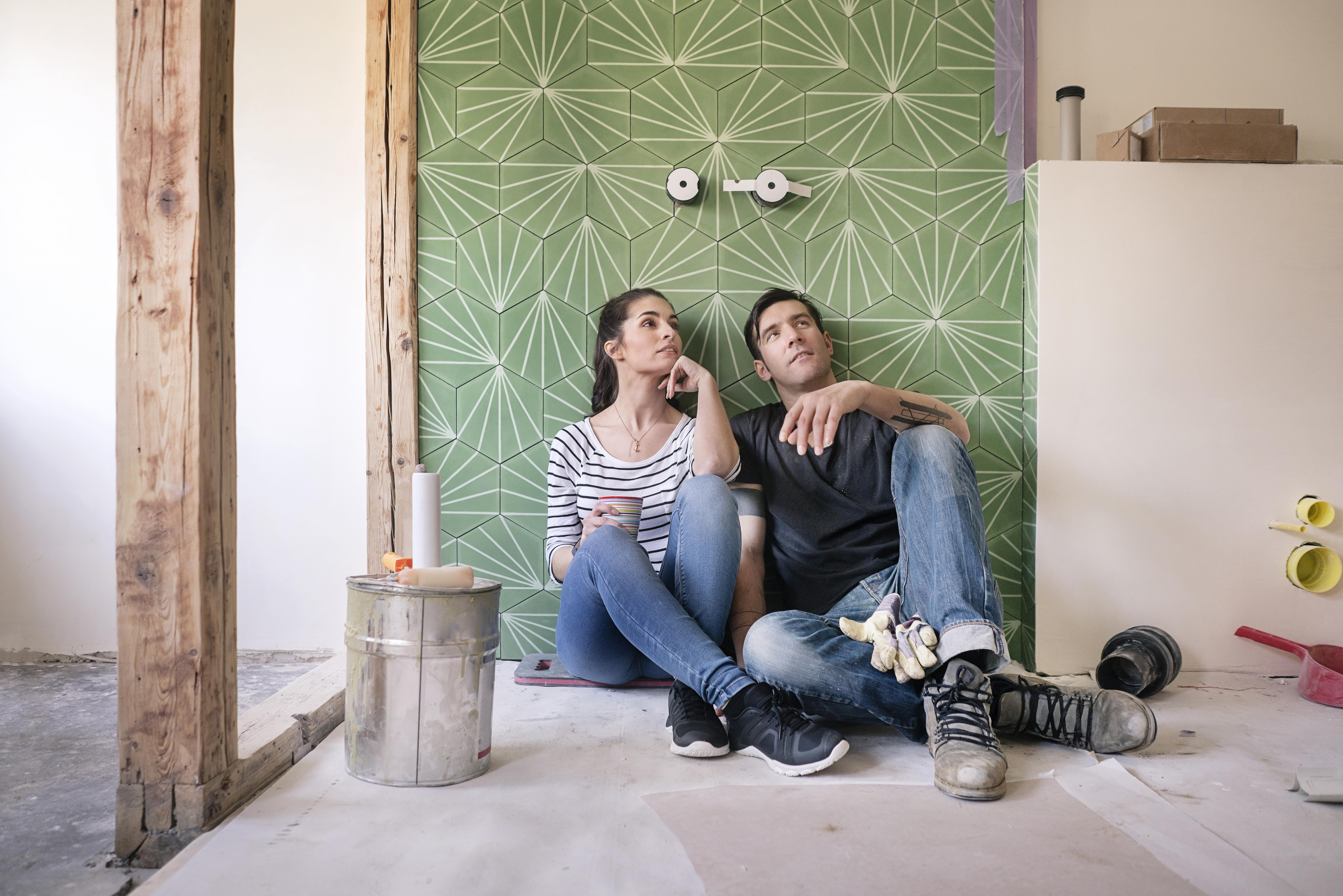 couple sitting on the floor of a bathroom being renovated