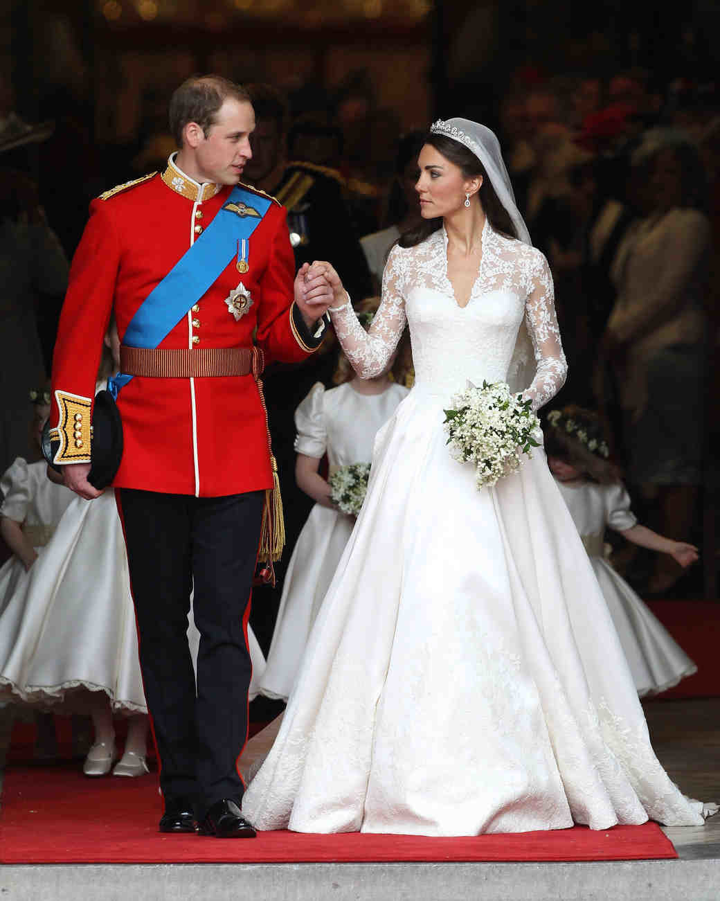An image of a royal bride and groom holding hands.