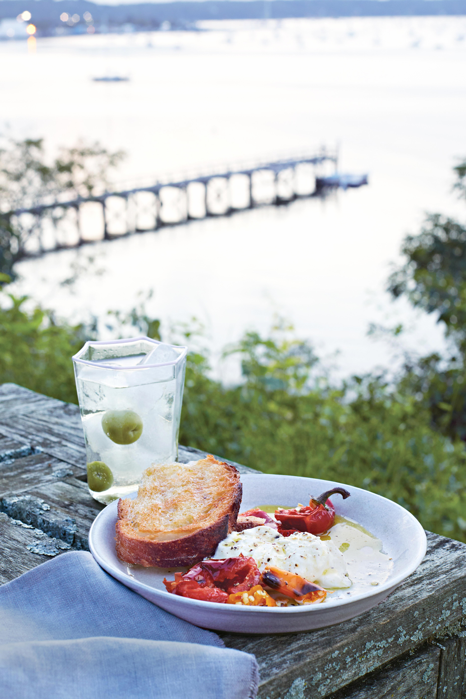 grilled bread and chiles with burrata placed on an outdoor picnic table