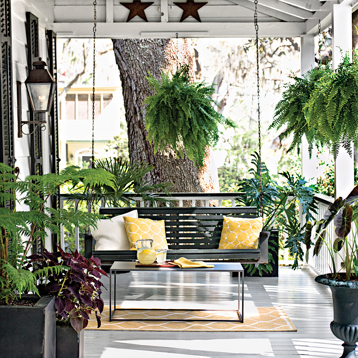 front porch with plants and black swinging chair with yellow accents