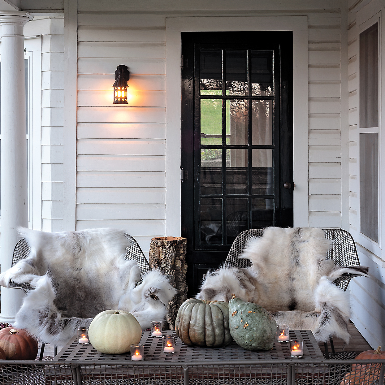 fur throws on wire chairs on front porch
