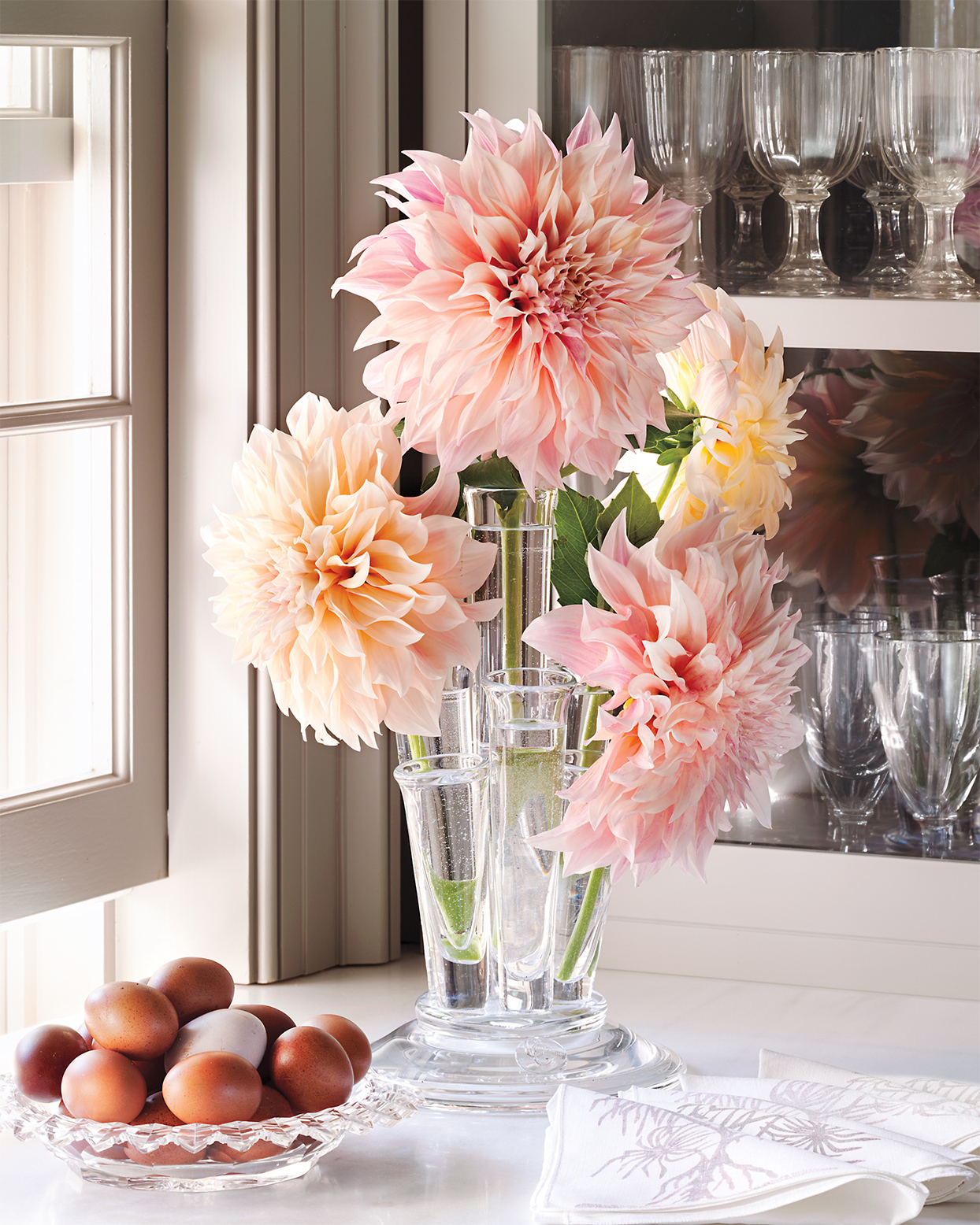 pink dahlias arranged in clear vases