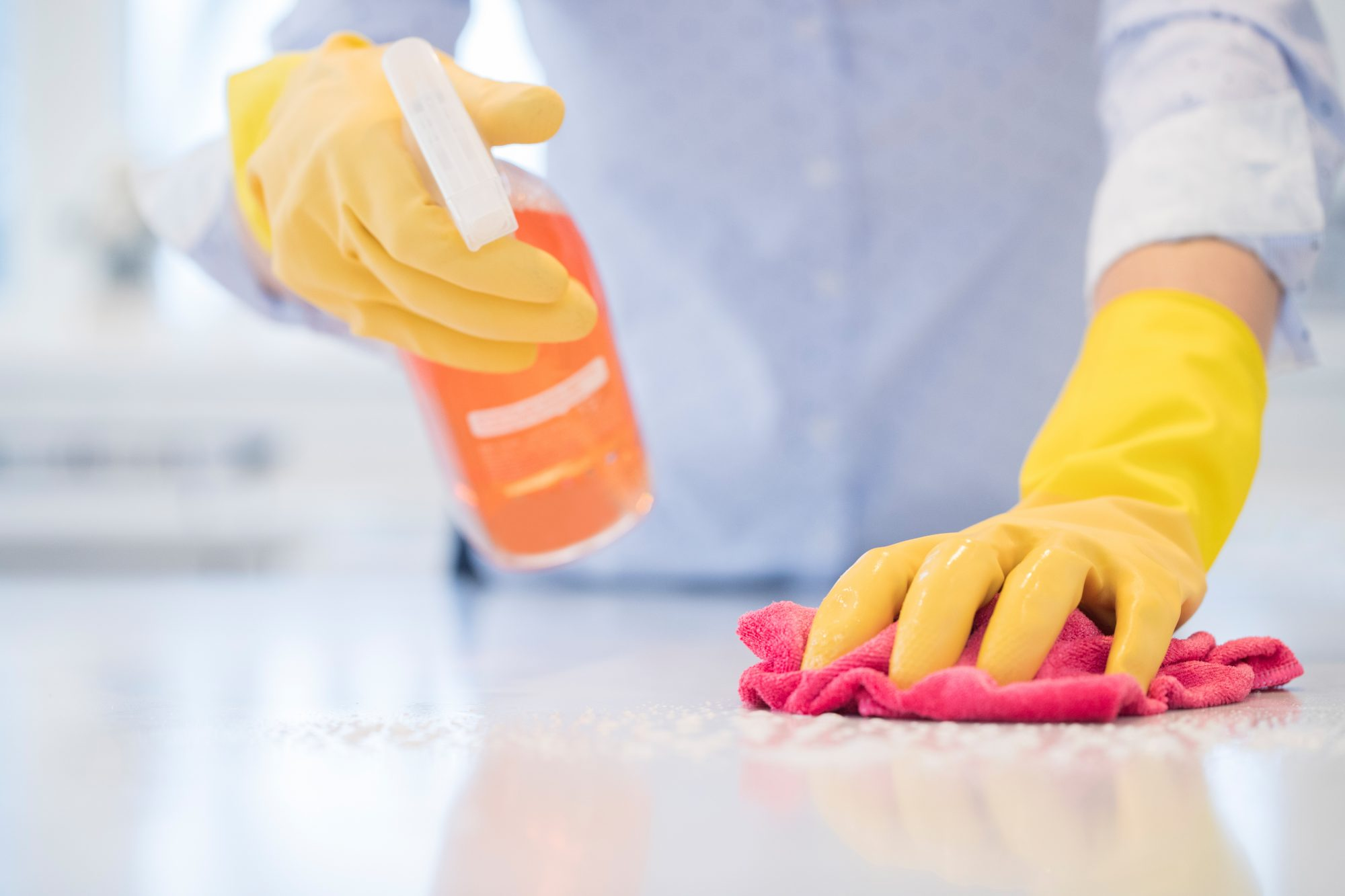 Woman Cleaning Countertop Wearing Gloves