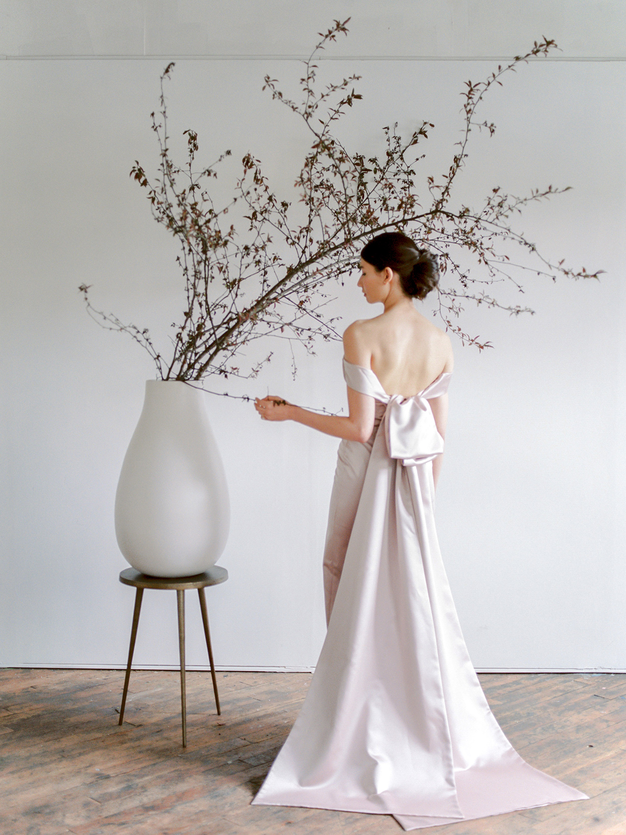 minimalist ikebana floral cherry blossoms and woman in pale pink dress