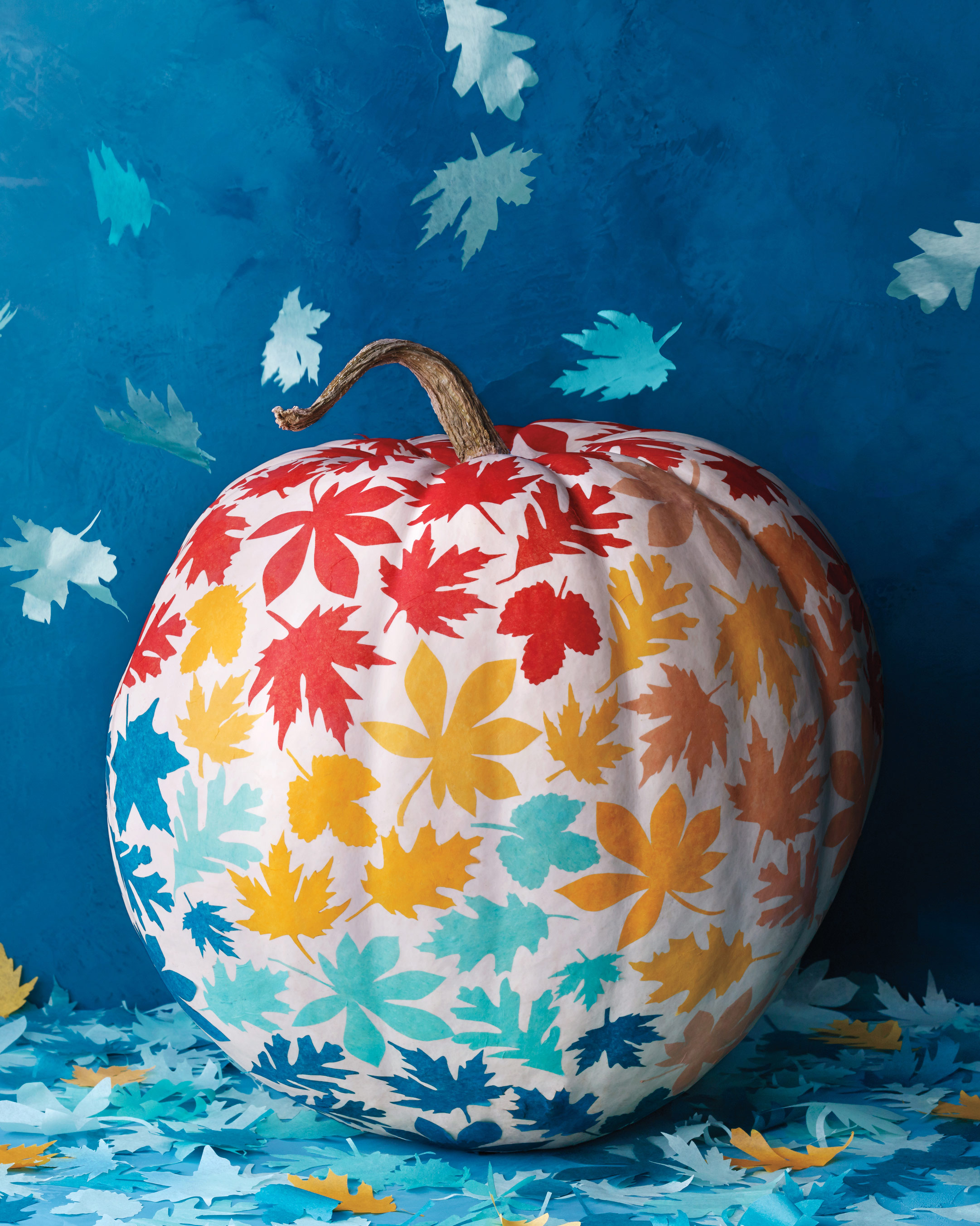 white pumpkin with painted leaves in red yellow light and dark blue