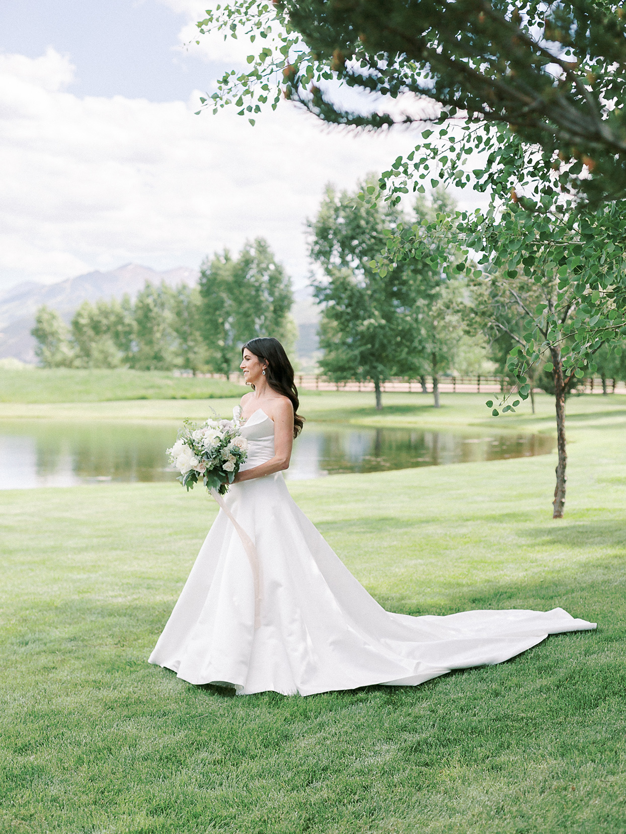 jessica aaron wedding bride standing in field with mountain backdrop