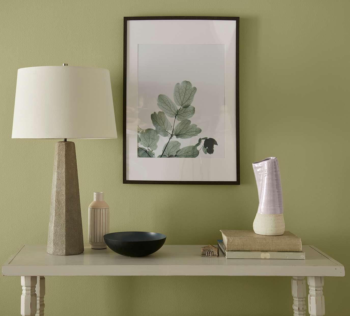 sage green wall with decorative neutral colored table