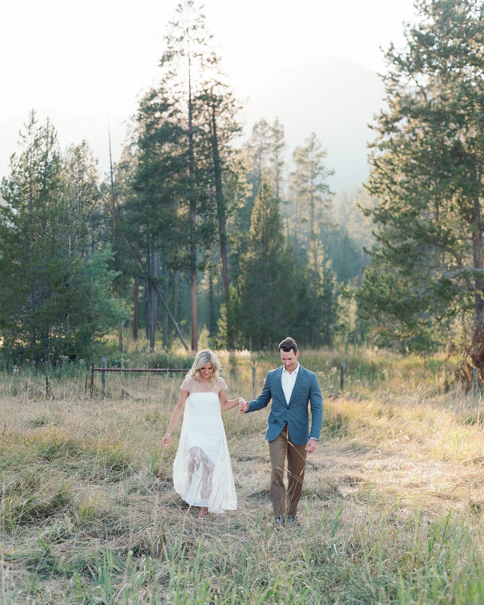 bride groom walking in wooded grass area