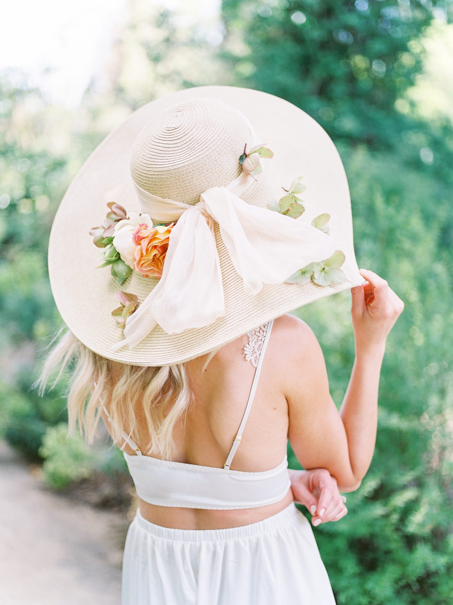 bride wearing flower hat during summer rehearsal dinner