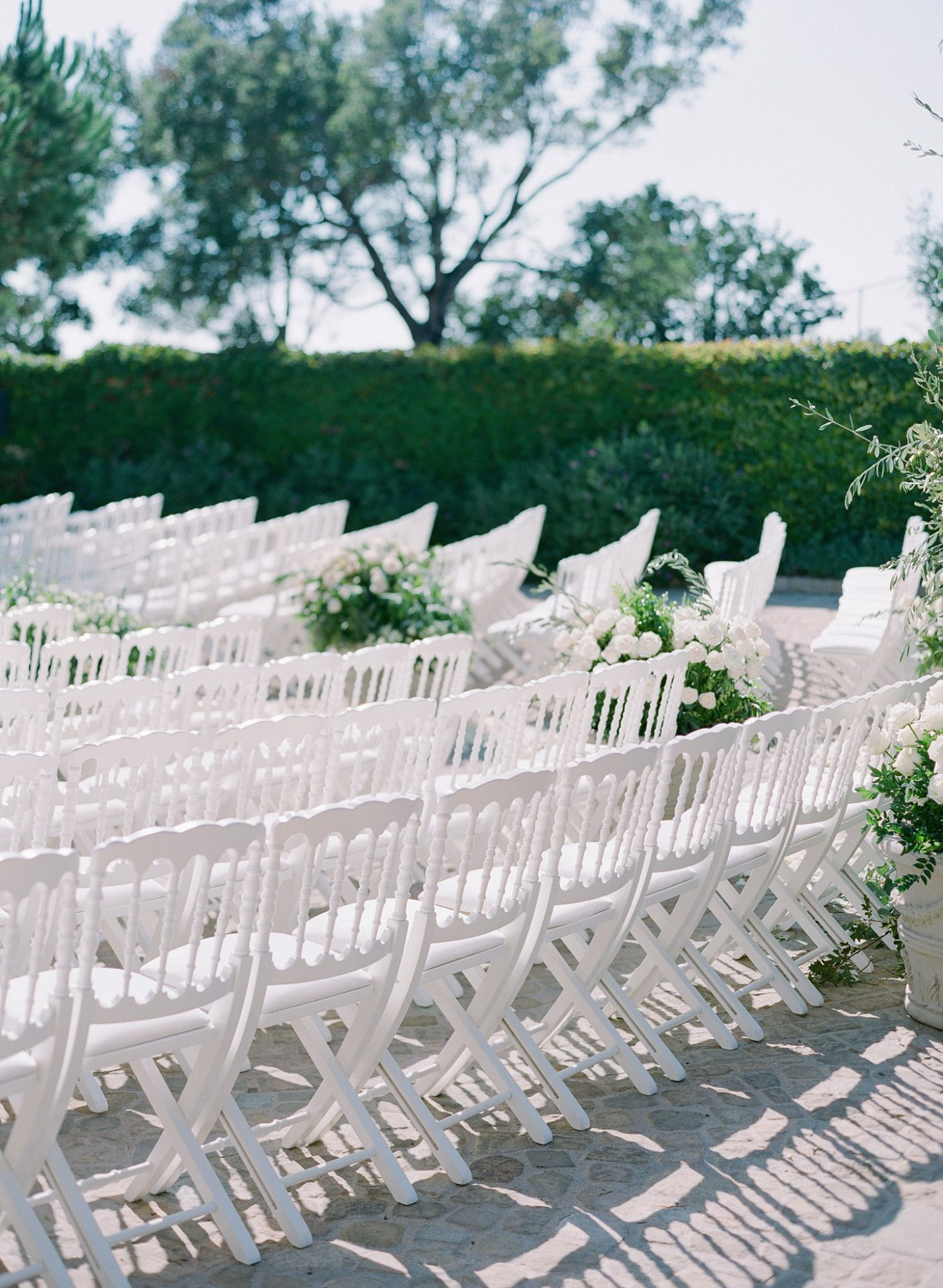 rows of white wedding ceremony chairs