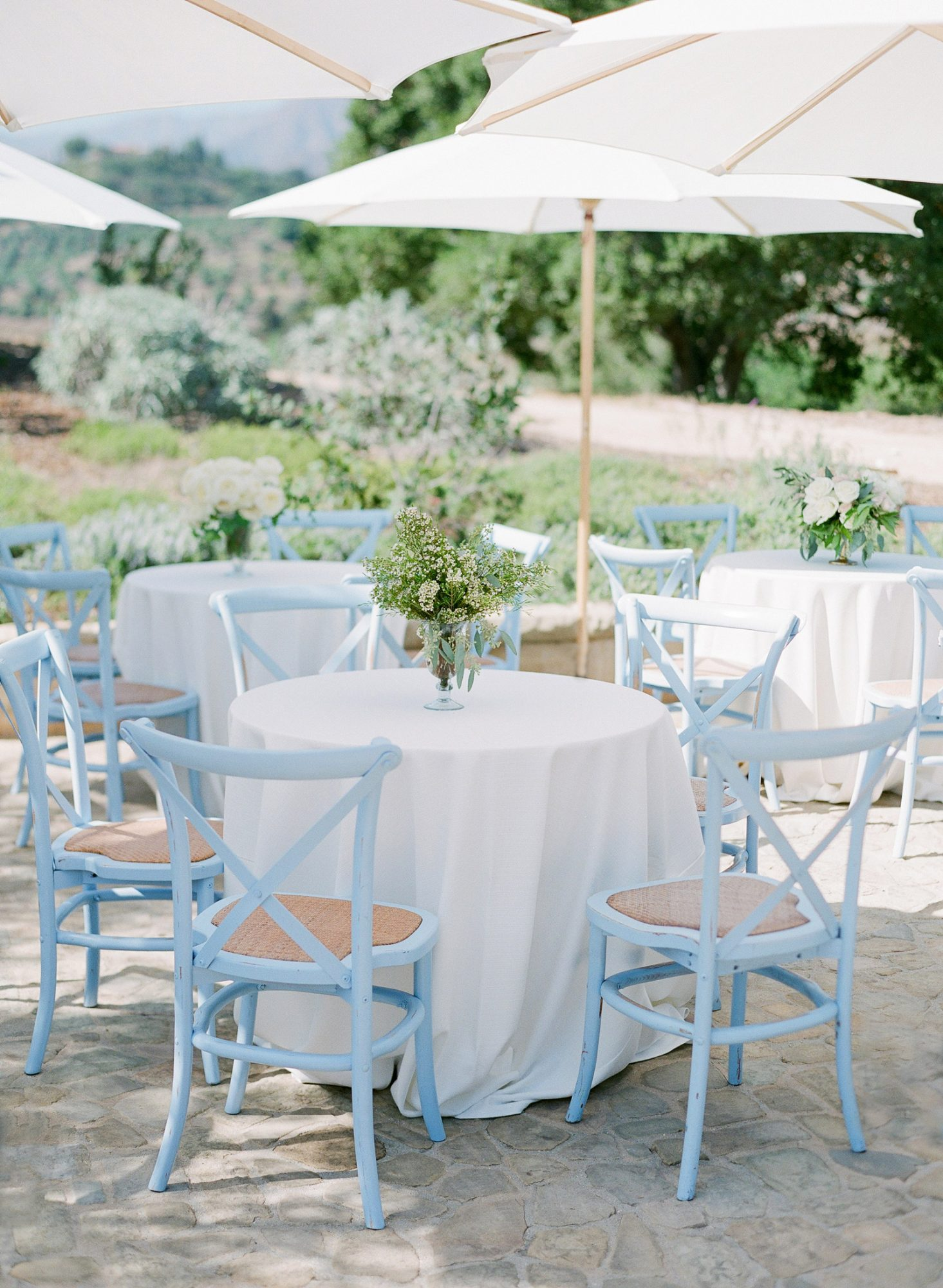 white tables with white umbrellas and light blue chairs