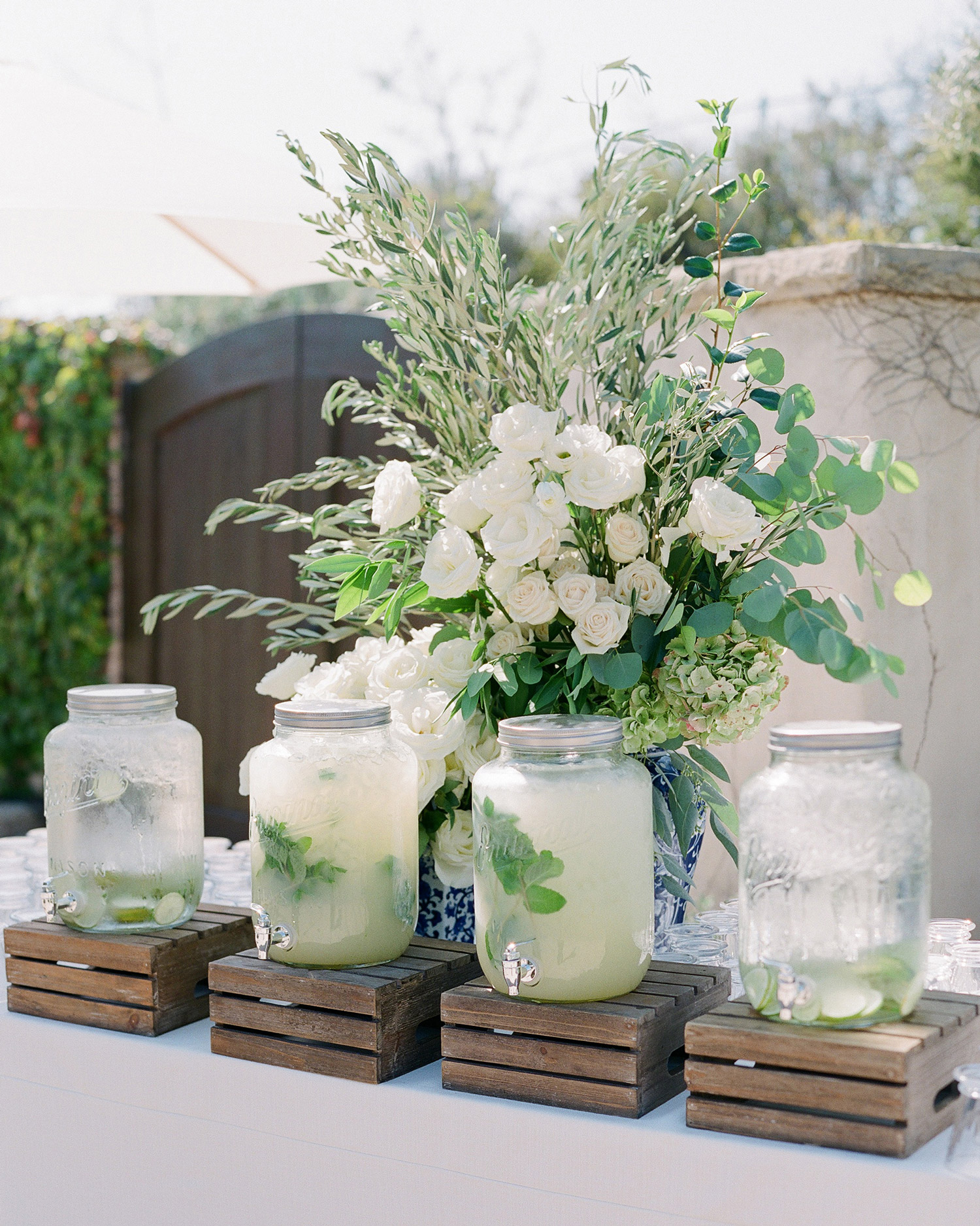 glass jugs of lemonade and water on wooden crates
