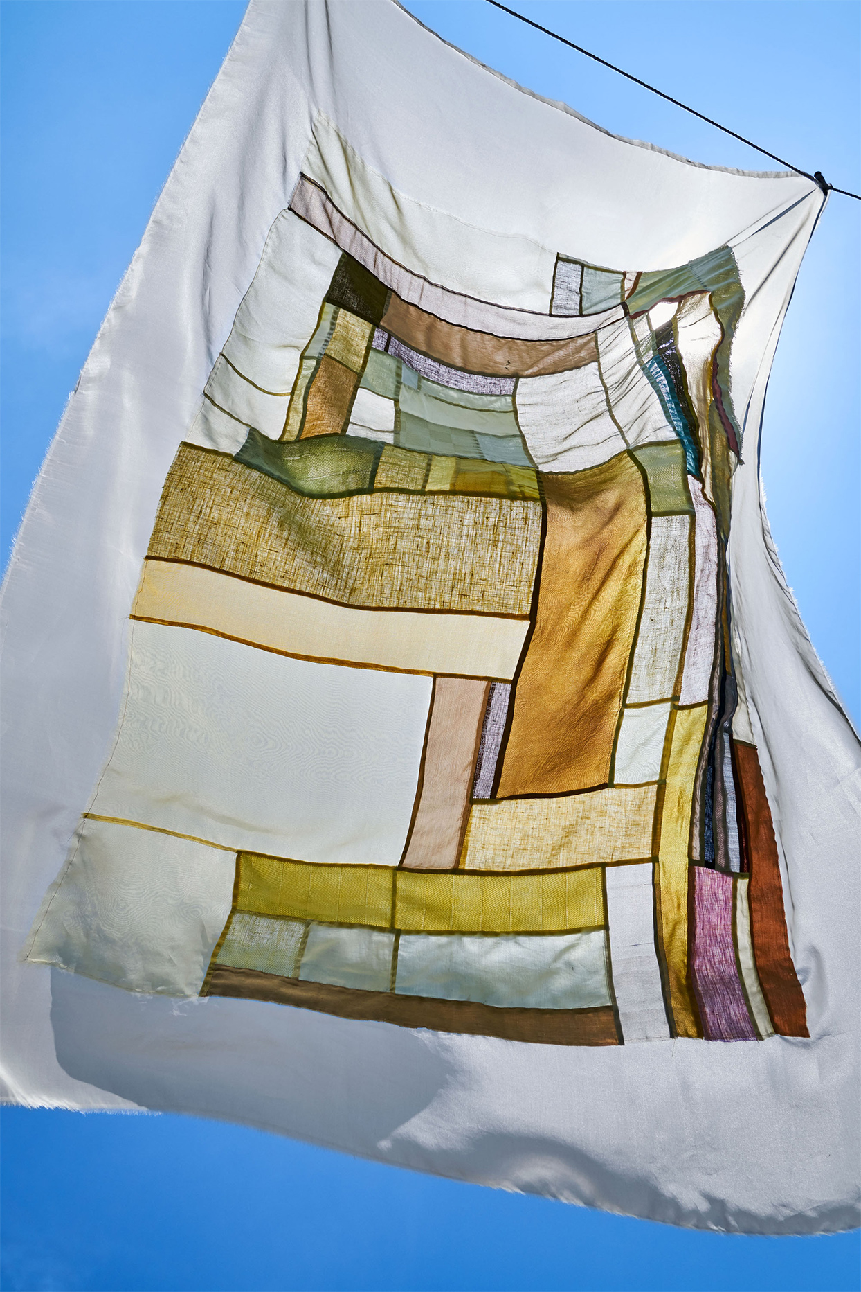 quilted naturally dyed textile hanging outdoors