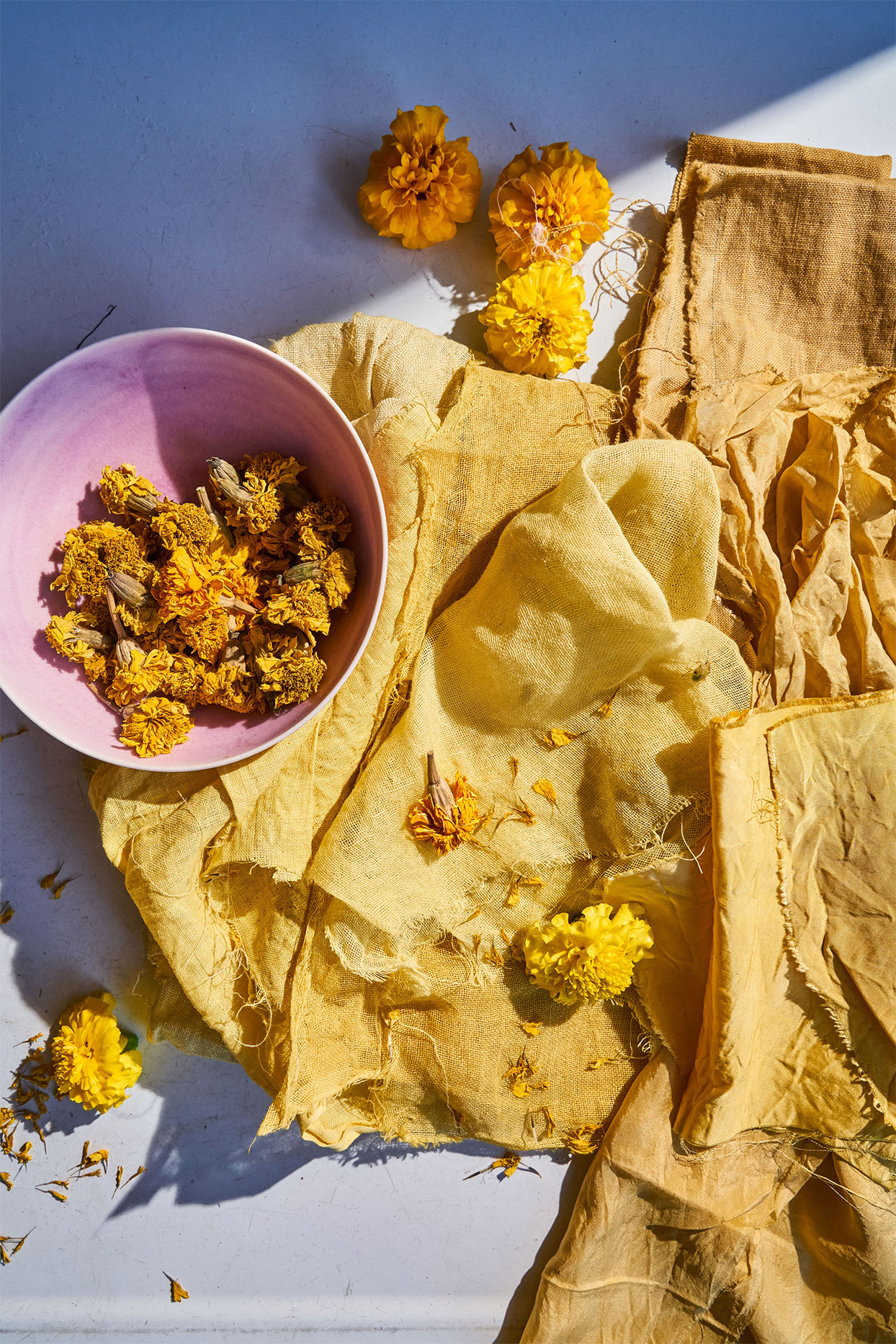 naturally dyed fabrics with dried marigolds in a pink bowl