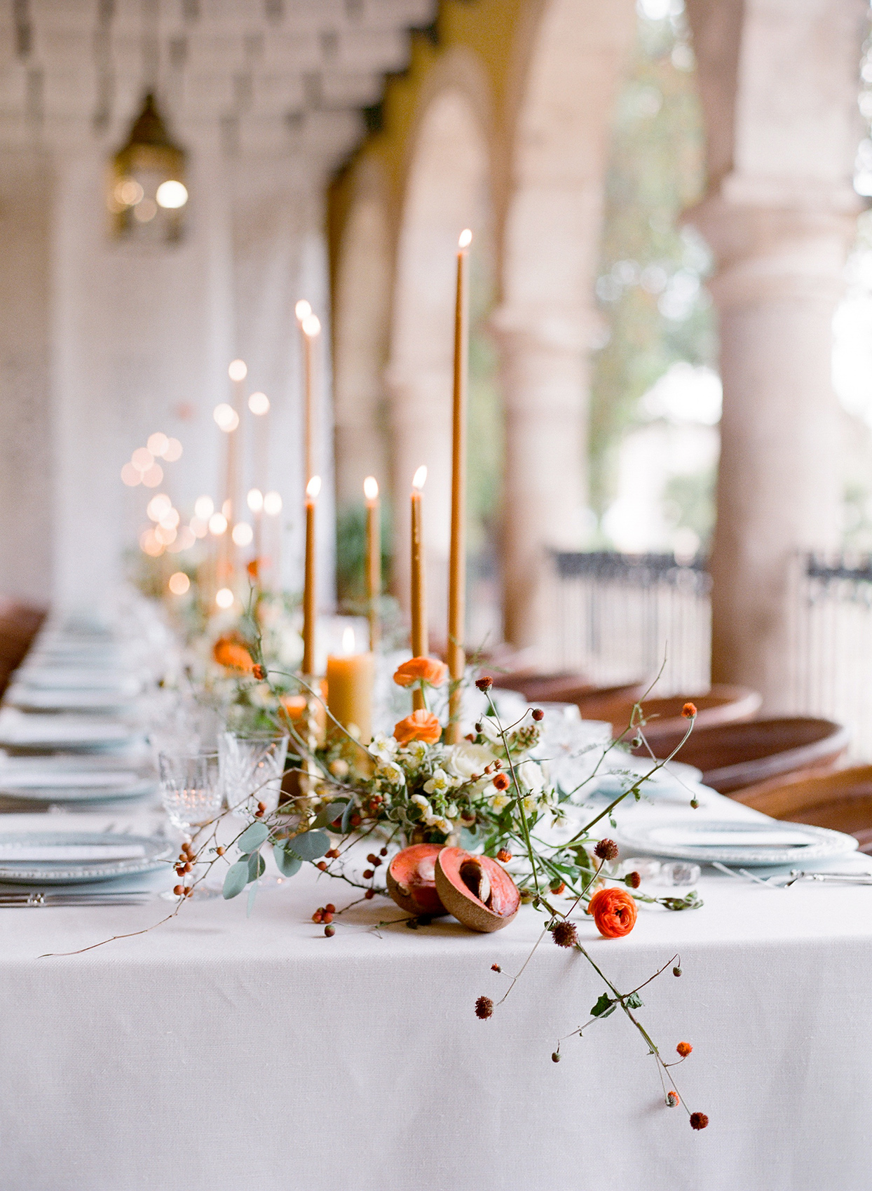colorful red and orange centerpieces on long white table